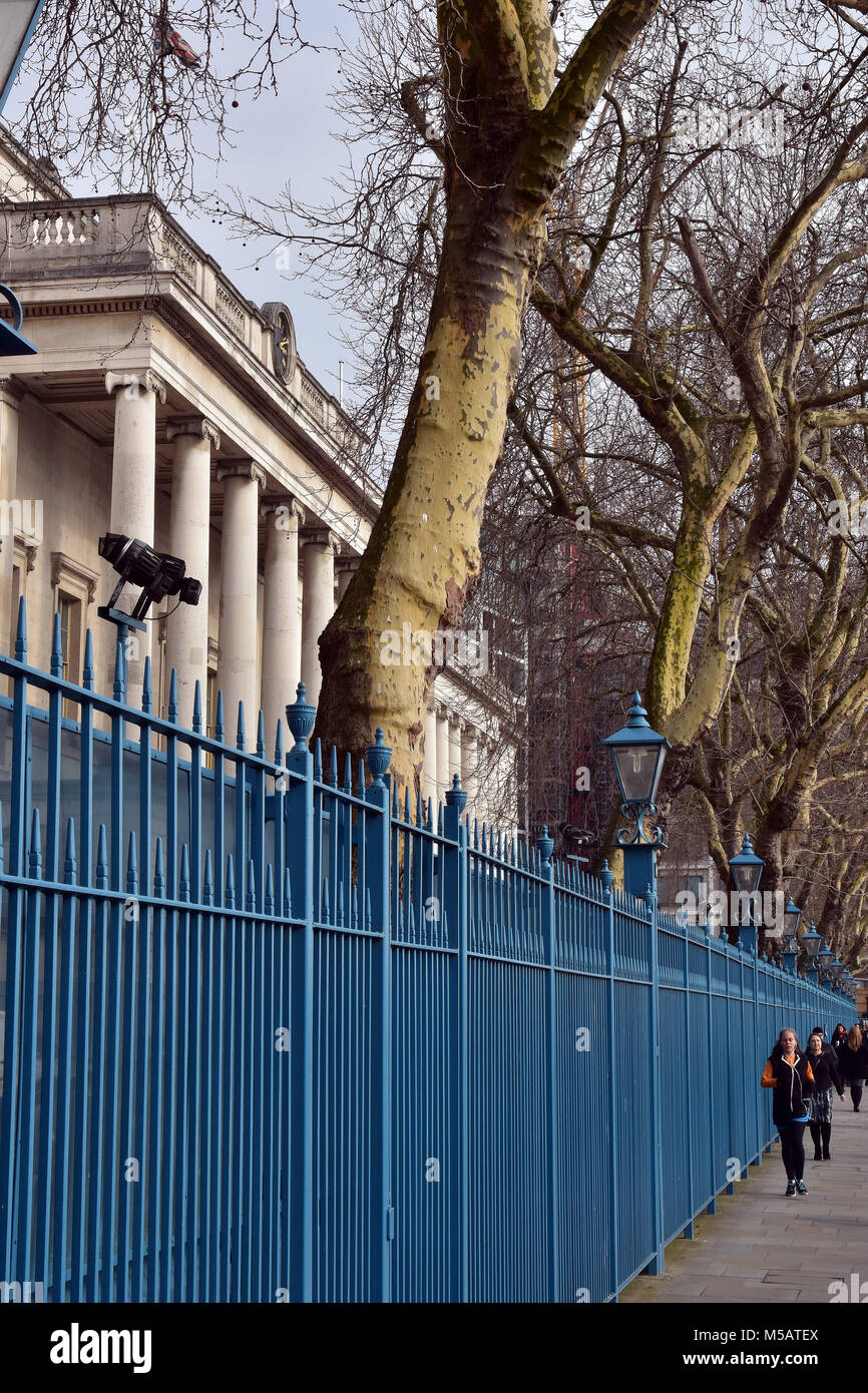 A classical styled buildings and some cast iron railings on the bank of the river thames in london. Typically urban - Stock Image