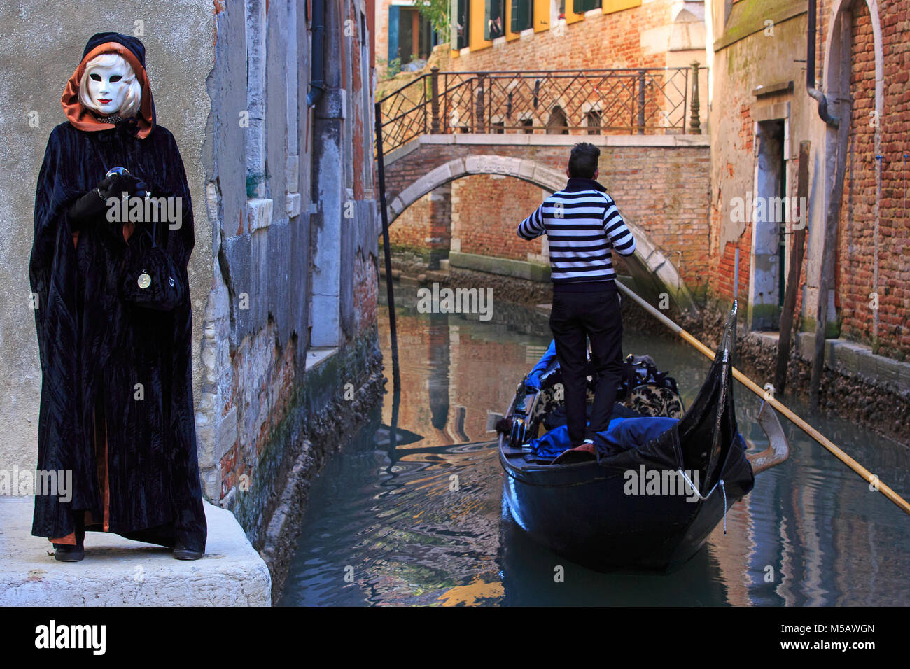A gondolier rowing past a female fortune teller during the Carnival of Venice (Carnevale di Venezia) in Venice, - Stock Image