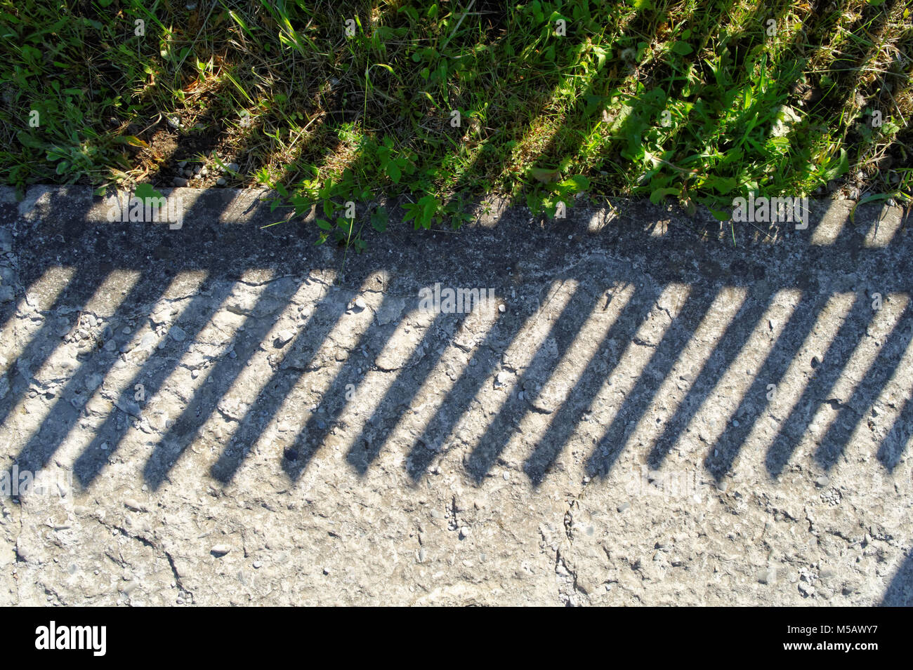 shadow of the wooden fence along the country concrete road - Stock Image