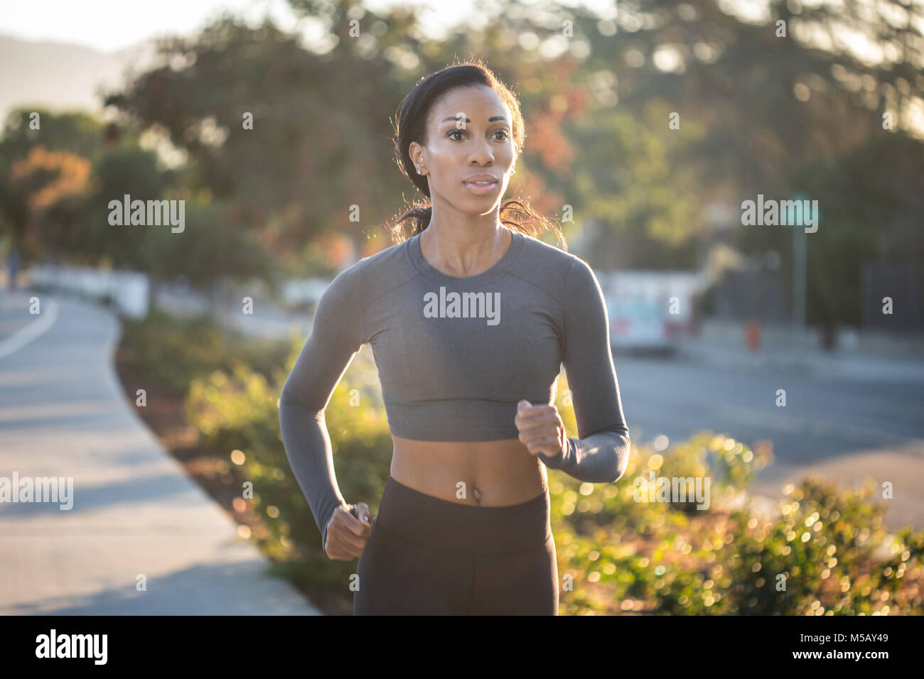 Inspired young woman running in the golden sunlight in the city park - Stock Image