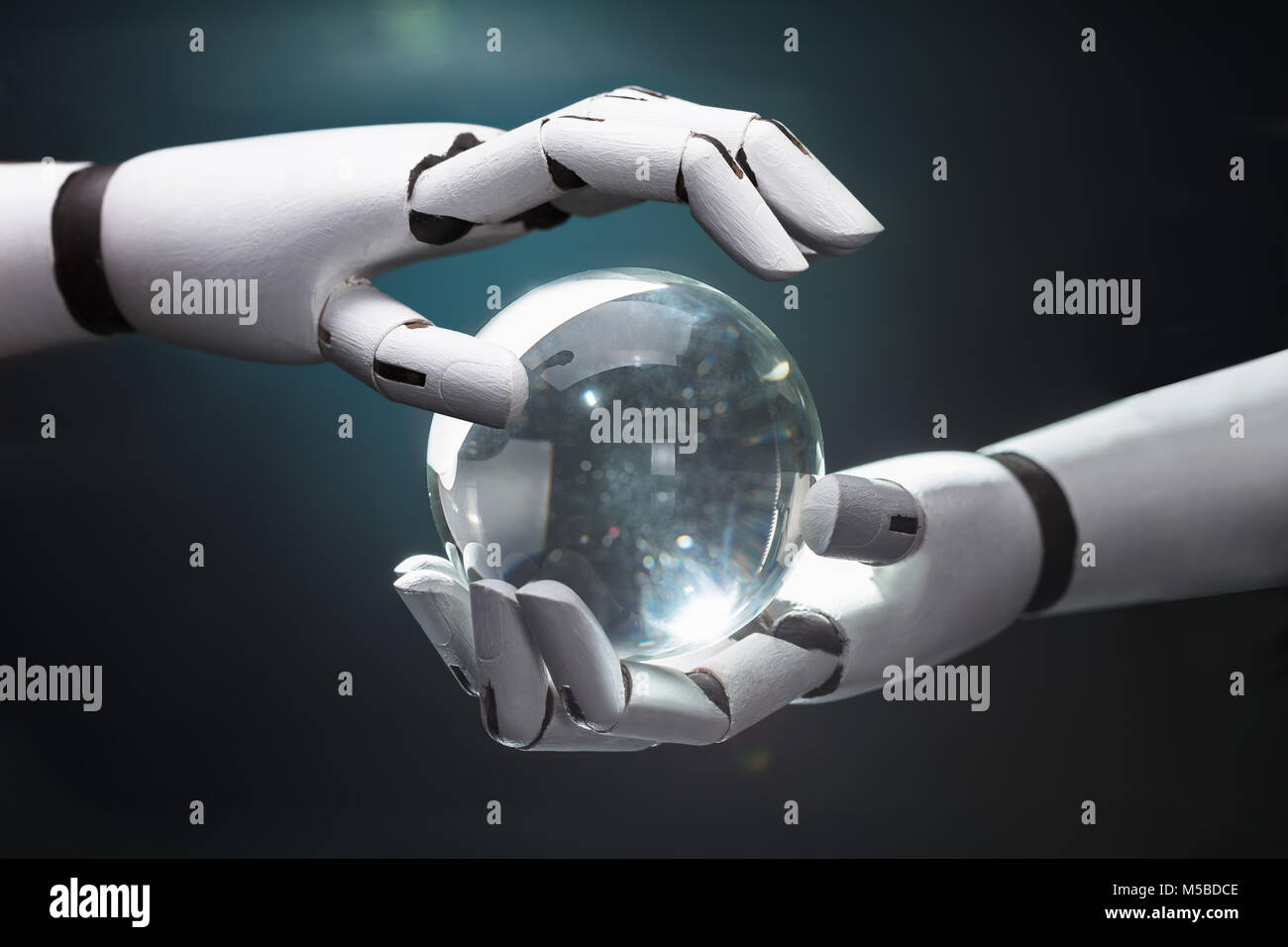 Close-up Of A Robot's Hand Predicting Future With Crystal Ball - Stock Image