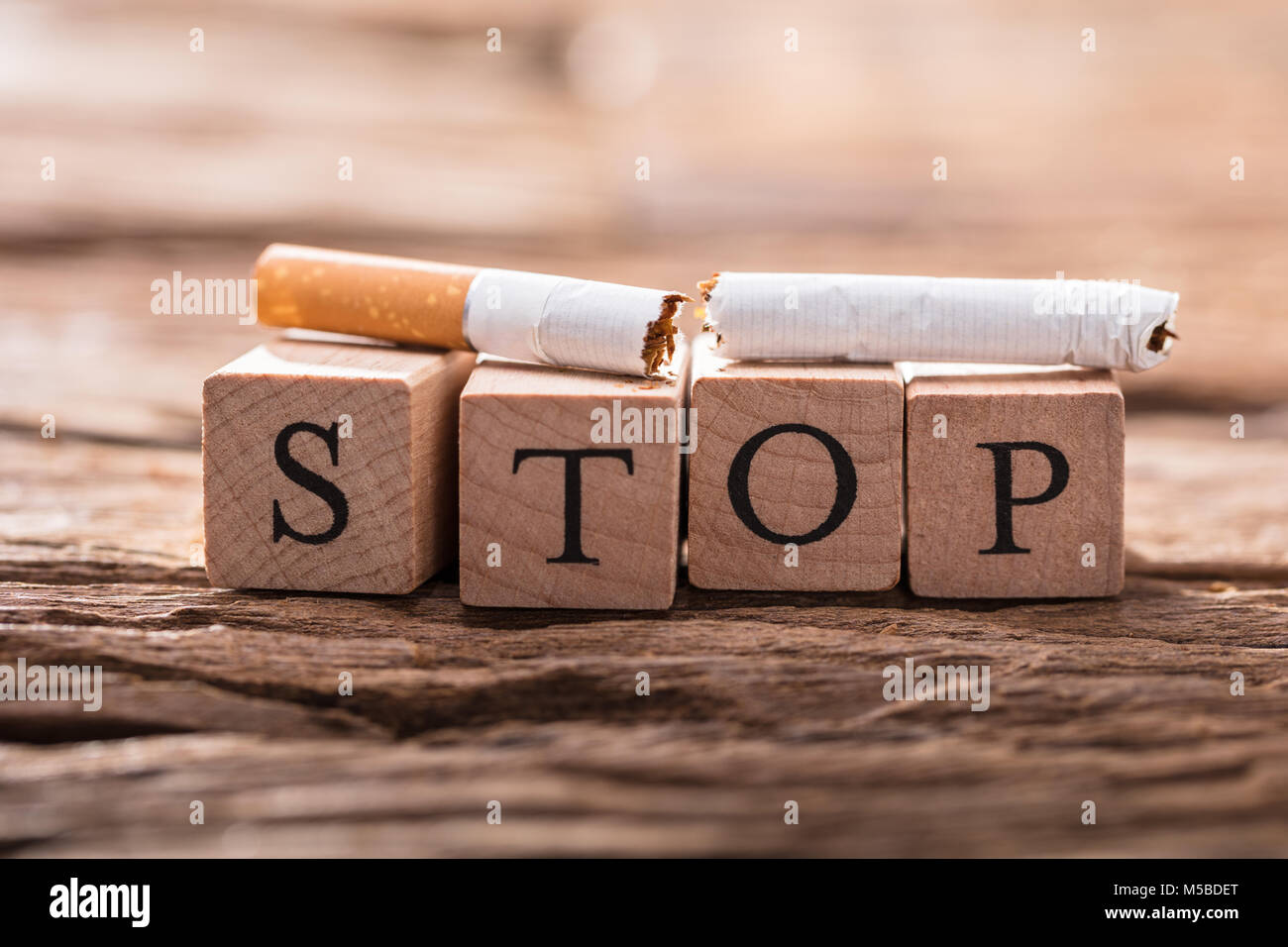 Close-up Of A Cigarette And Wooden Blocks Showing Stop Word On Desk - Stock Image