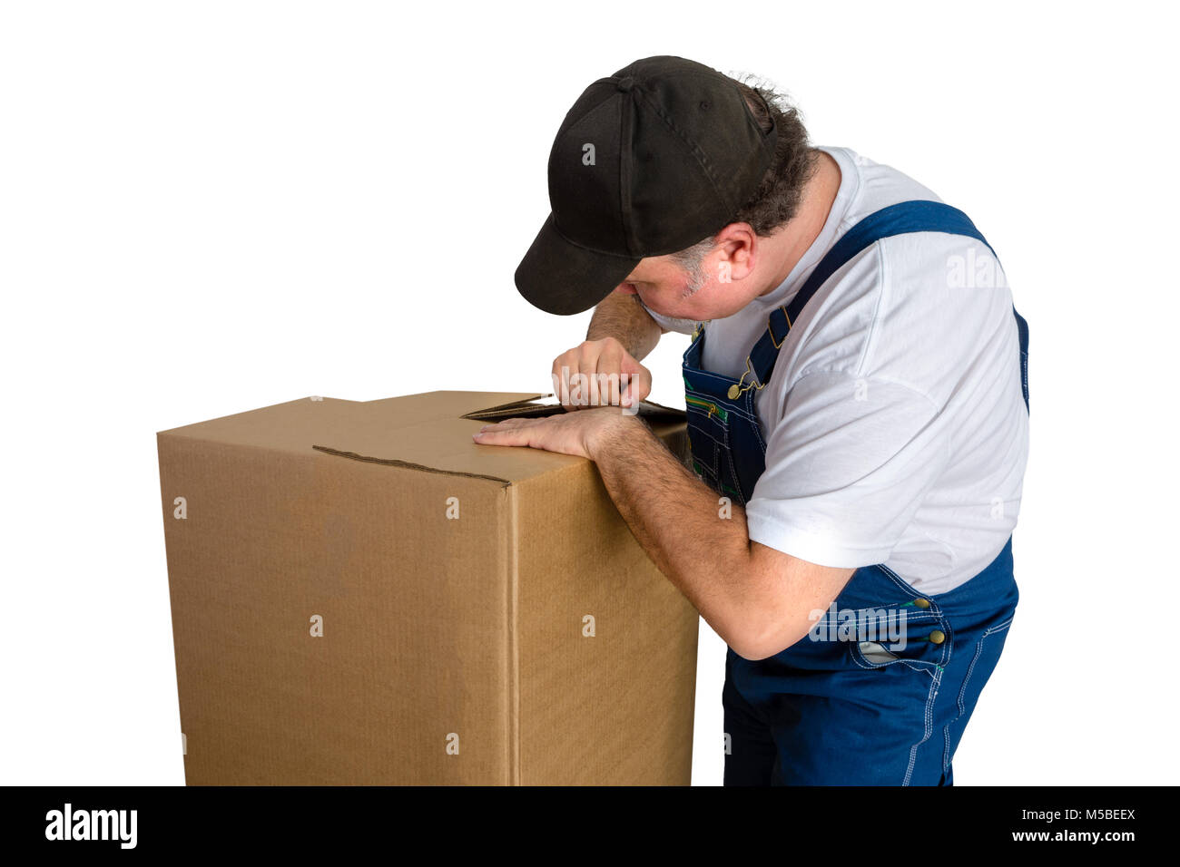 Male worker wearing dungarees opening cardboard box against white background - Stock Image