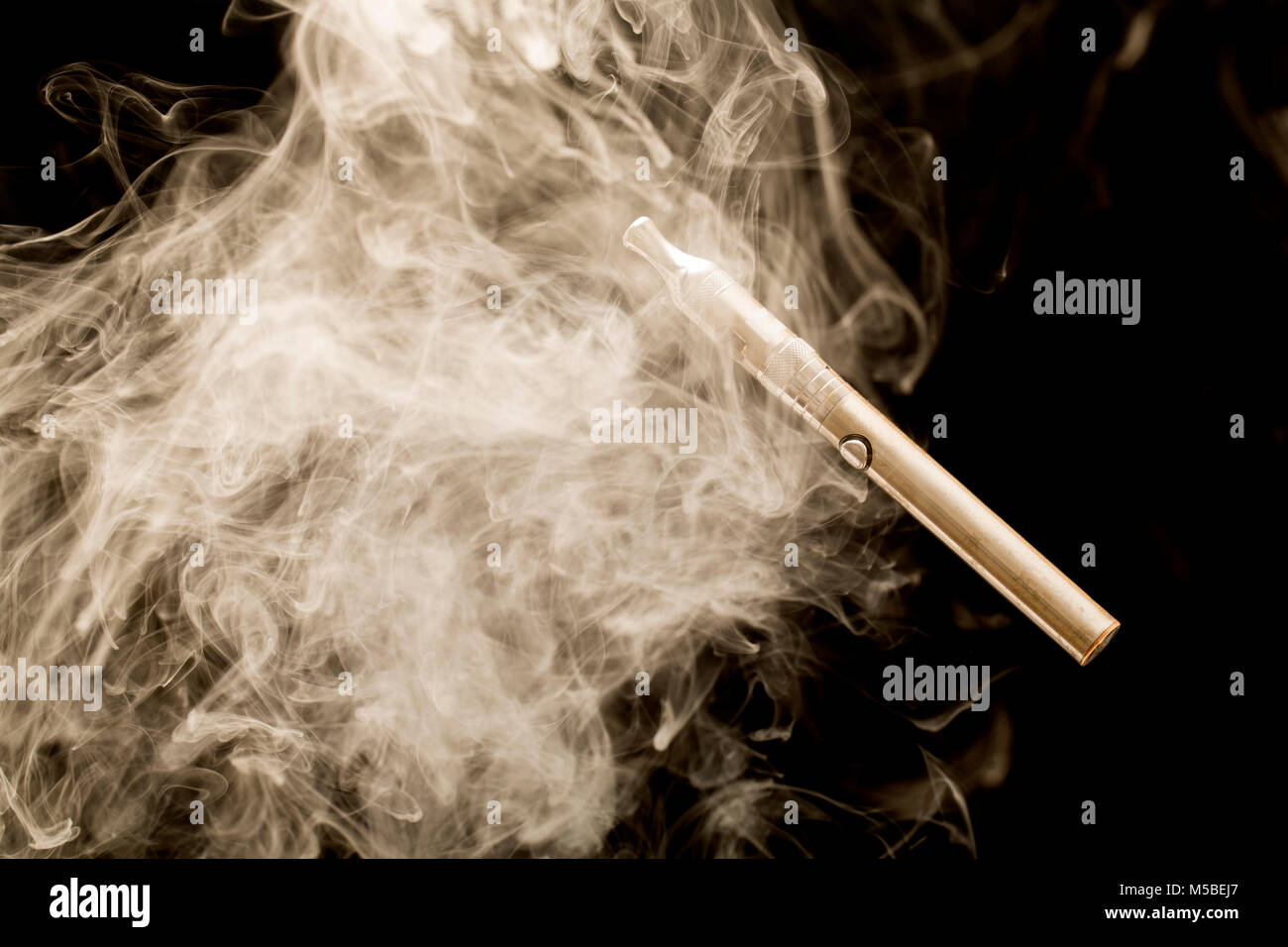 Electric cigarette or E cigarette surrounded by vapour from its E liquid. England UK GB. Photographed on a black - Stock Image