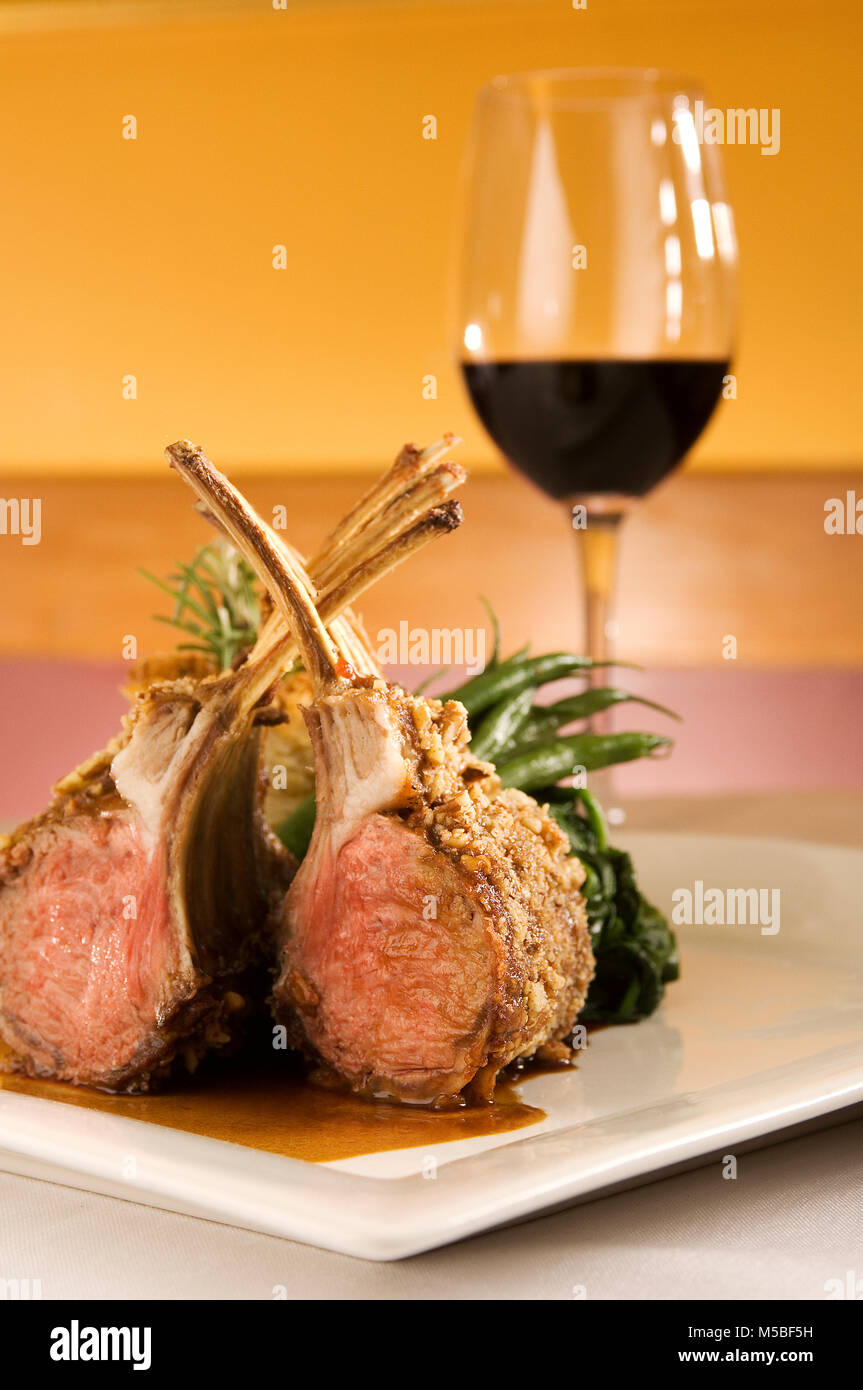 Rack of lamb chops ribs on bone upright plated, green vegetables, red wine in restaurant setting, vertical, cover, - Stock Image