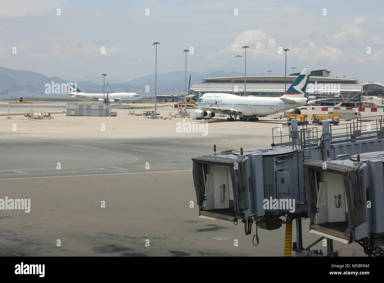 Two planes of the Cathay pacific company in the hub of Chek Lap kok airport in Hong Kong. - Stock Image