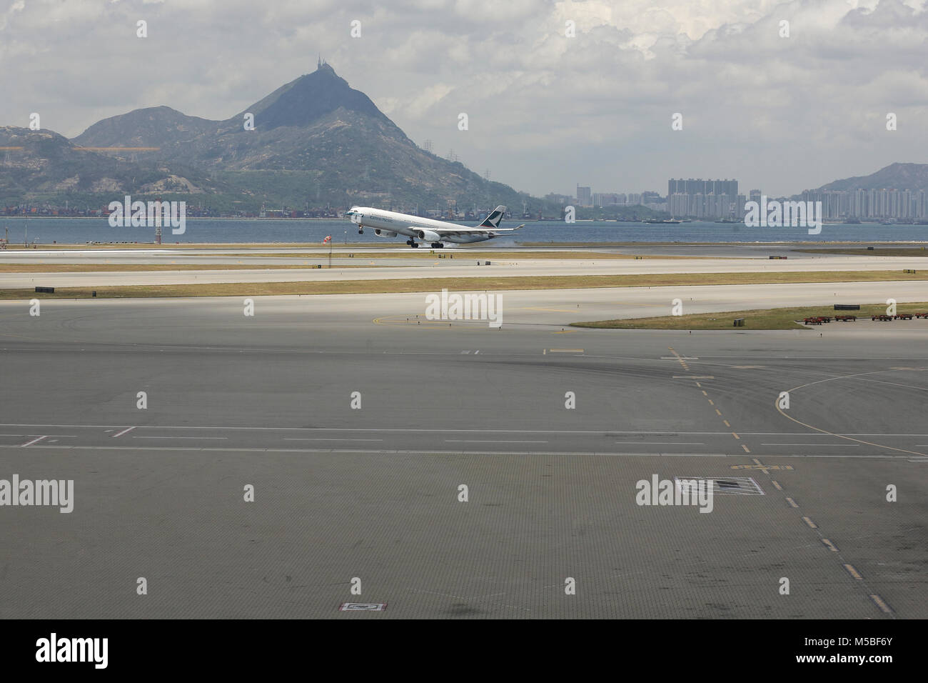 A plane from Cathay Pacific is landing off the Hong Kong Chek lap kok airport. - Stock Image