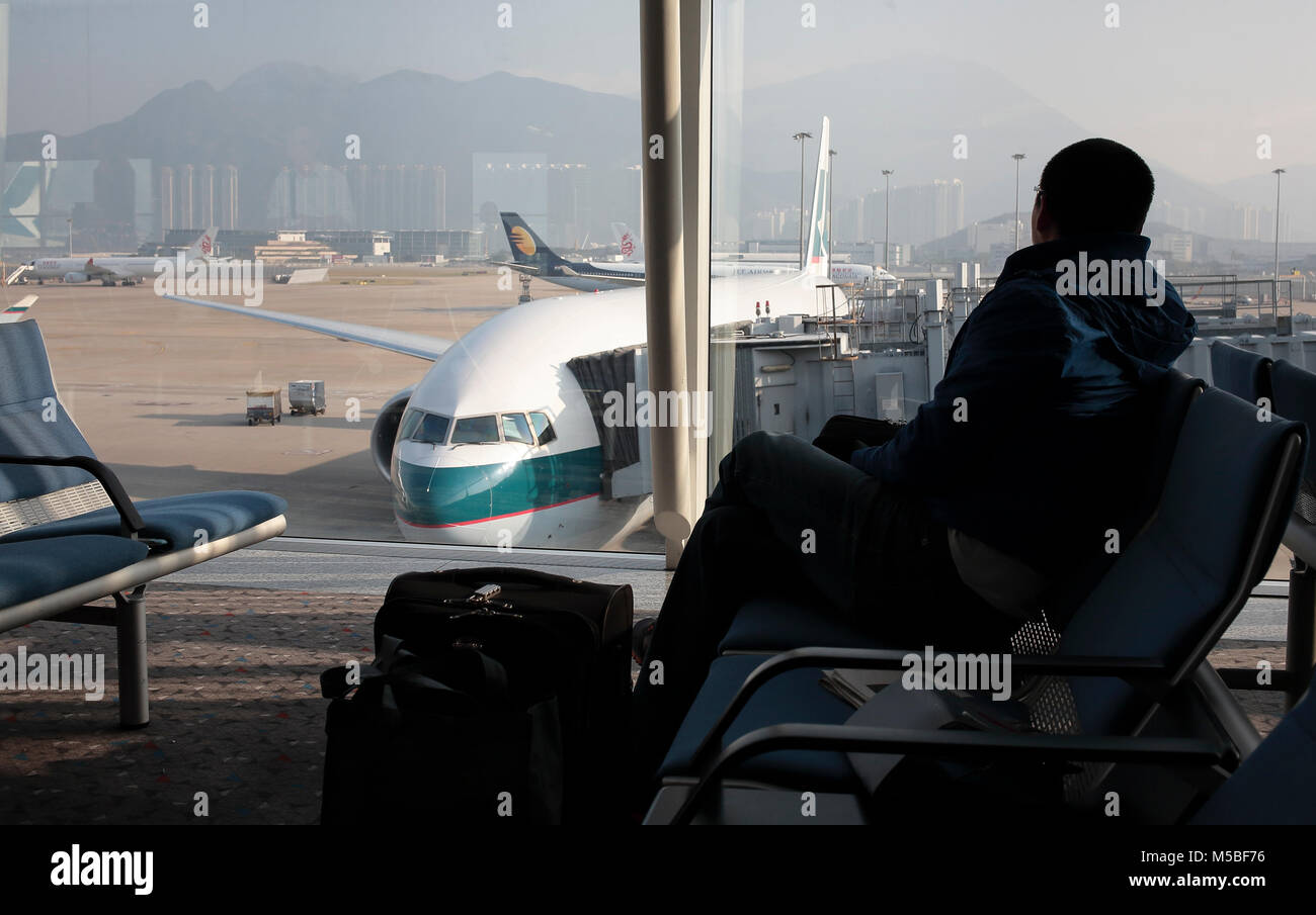 A passenger in the waiting room is looking at planes connected to the hub at the Hong Kong Chek lap Kok  airport. - Stock Image