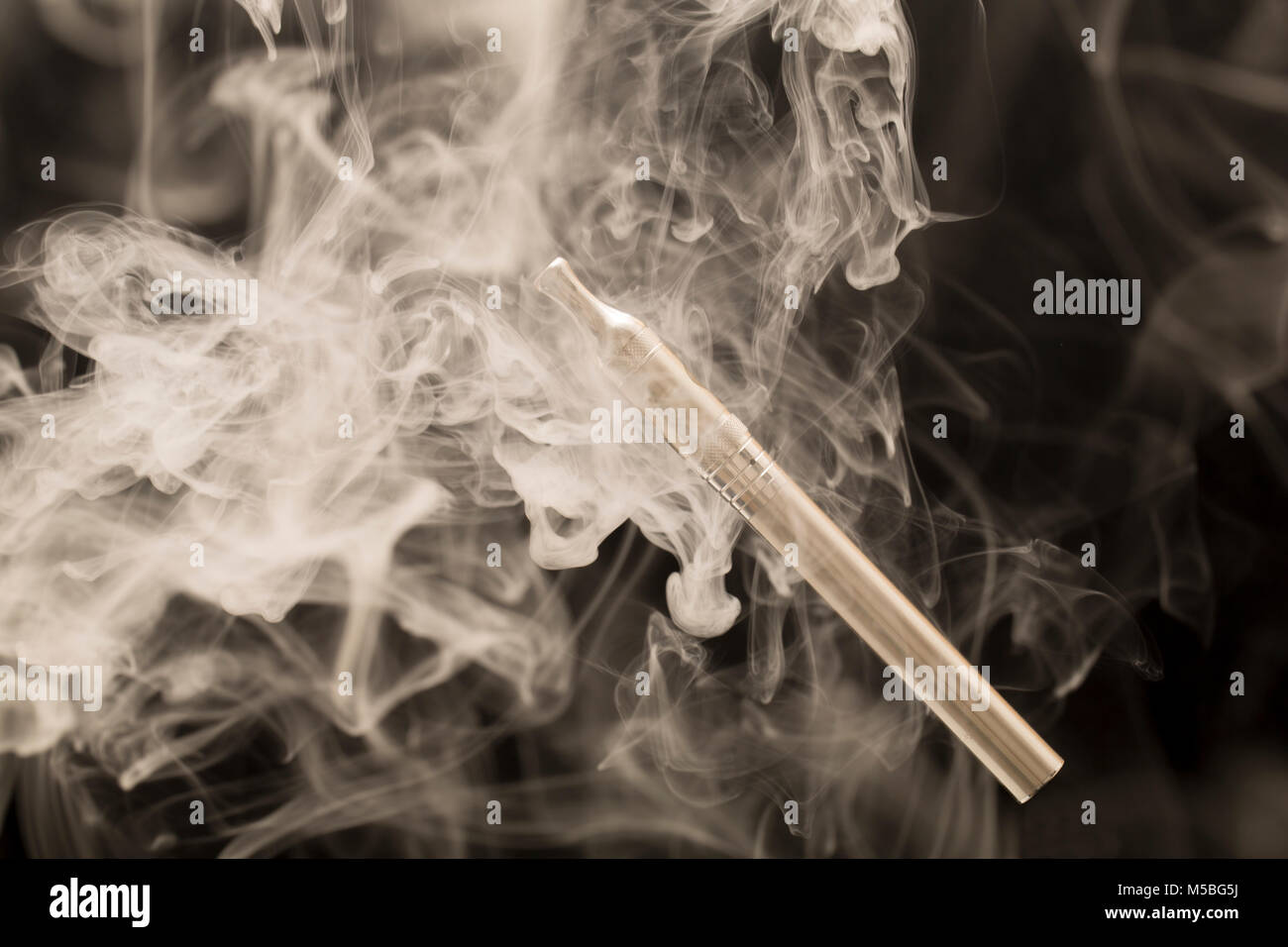 Electric cigarette or E cigarette surrounded by vapour from its E liquid UK GB - Stock Image