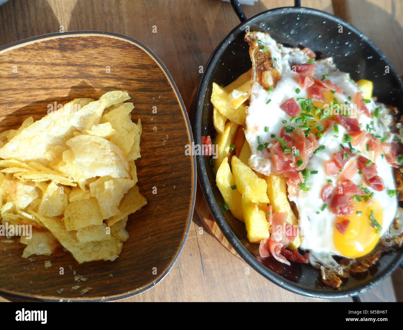 A dish of fried potato chips/fries topped with fried eggs, bacon and fresh chopped Chives served in a Spanish tapas - Stock Image