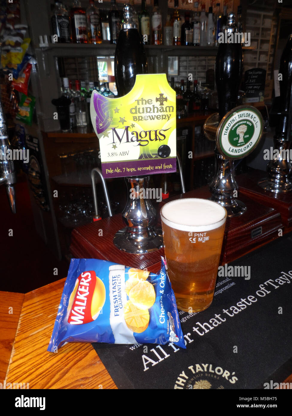 pint of Durham Brewery Pale ale, Magus, alongside the beer pump and pump clip and a packet of crisps/chips - Stock Image