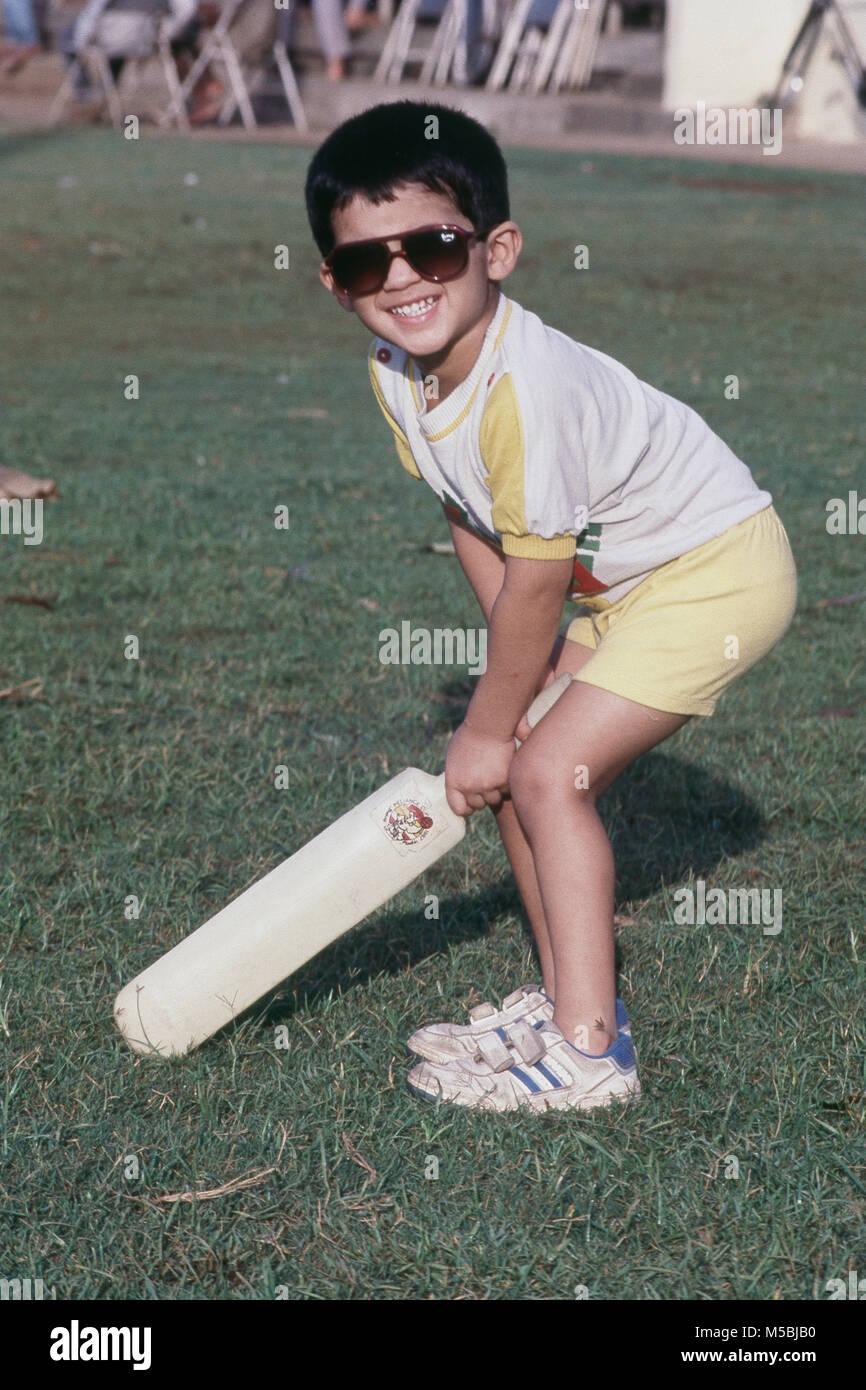 boy cheerfully playing cricket at Shivaji park, Dadar, Bombay, India - Stock Image
