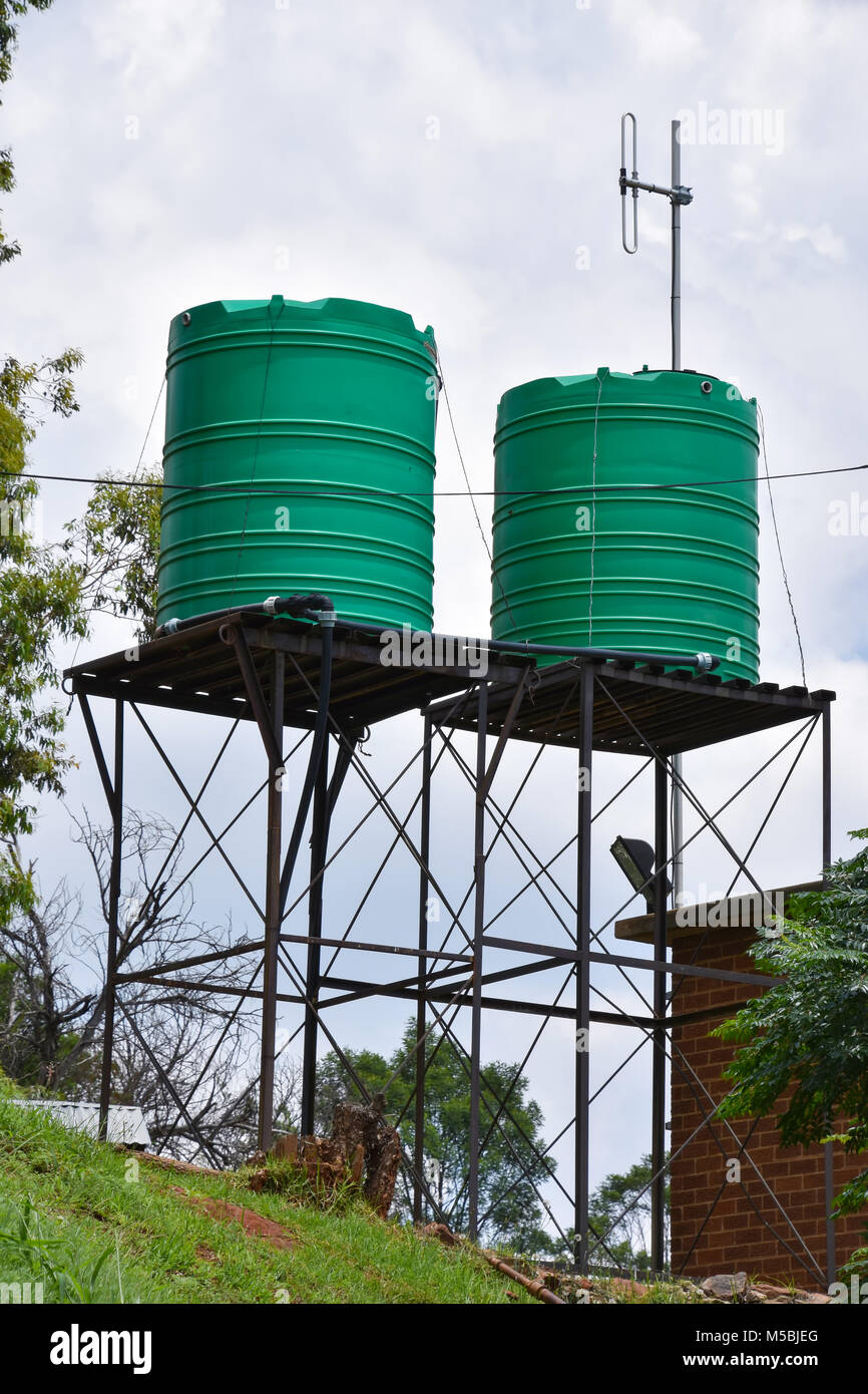 Green plastic water tanks on an elevated structure commongly used in Southern Africa & Green plastic water tanks on an elevated structure commongly used in ...