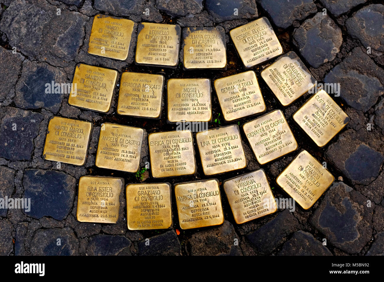 cobblestone-size concrete cube bearing a Stolperstein,a brass plate inscribed with the name and life dates of victims - Stock Image