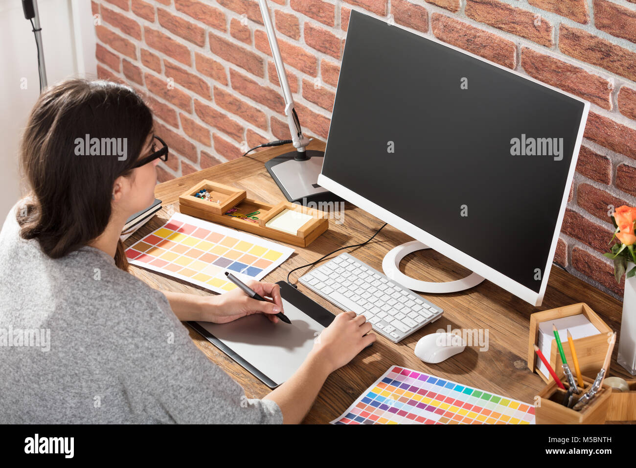 Young Female Graphic Designer Using Graphic Tablet With Color Samples On Desk Stock Photo