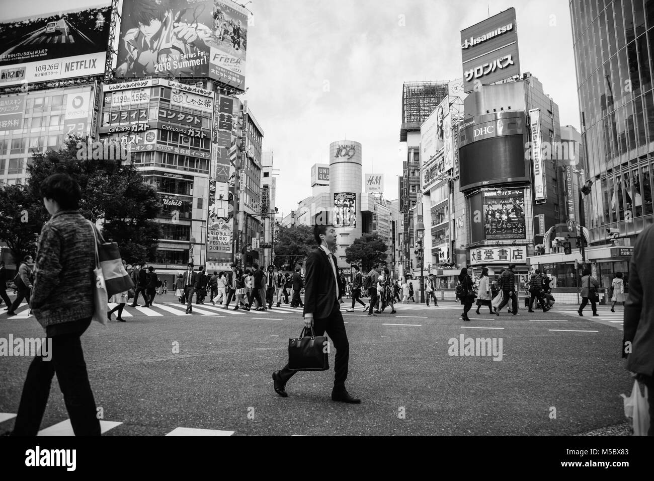 a business man crosses the street in Shibuya, Tokyo - Stock Image