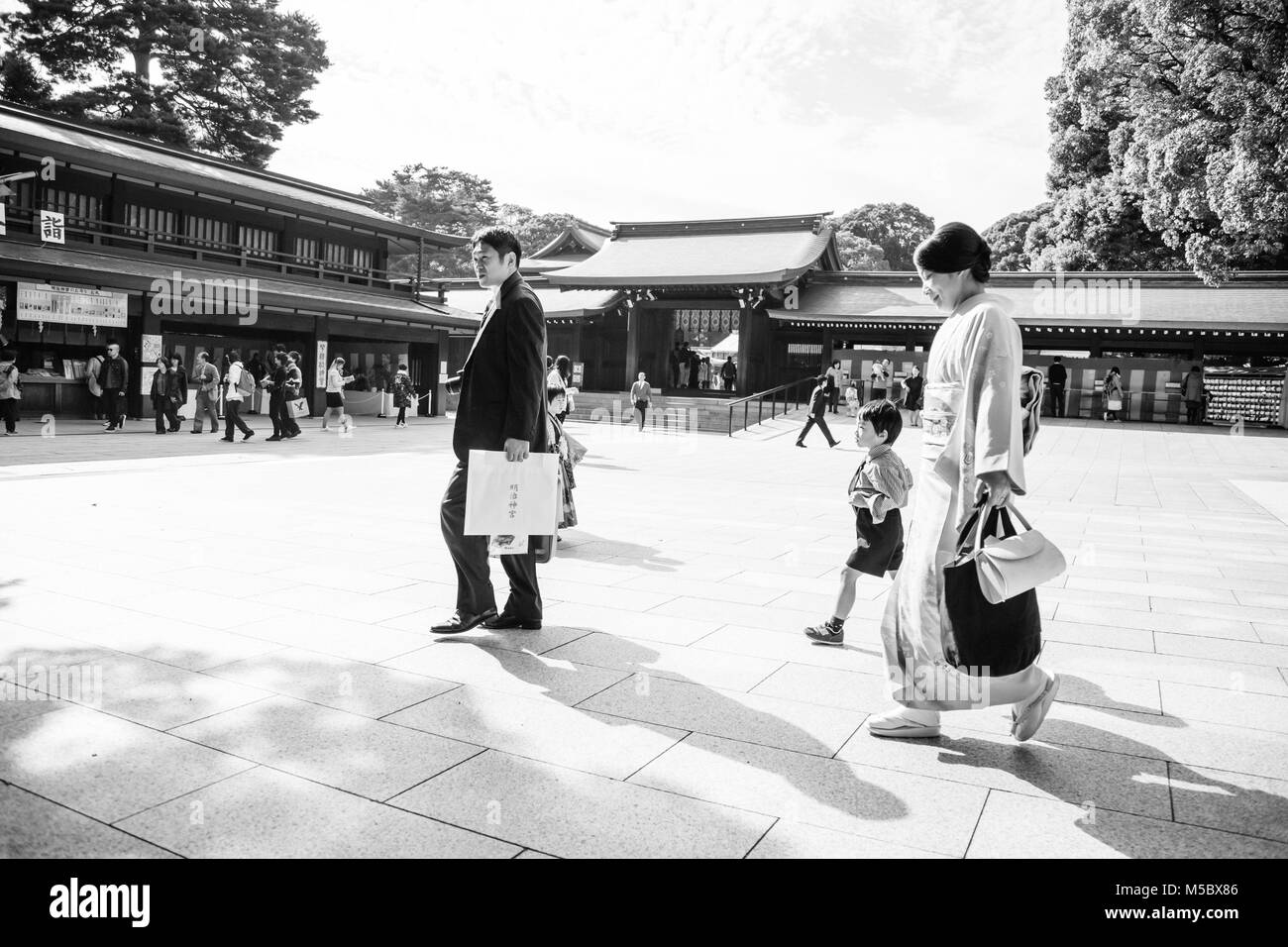 A family walks through the grounds of Meiji Jingu Shrine during the Grand Autumn Festival - Stock Image