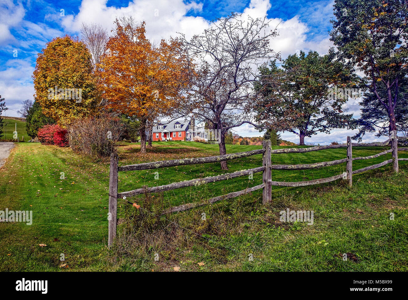Red brick Cape style home with a mossy split-rail fence, green lawn and colorful Autumn foliage in Franconia, NH, - Stock Image