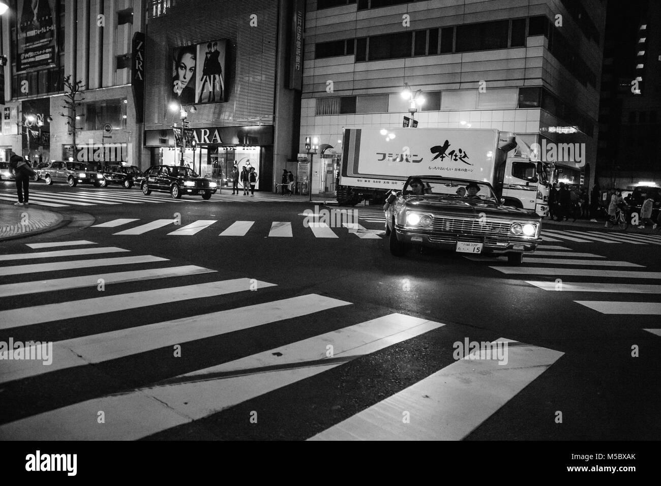 Vintage car cruising a city street - Stock Image