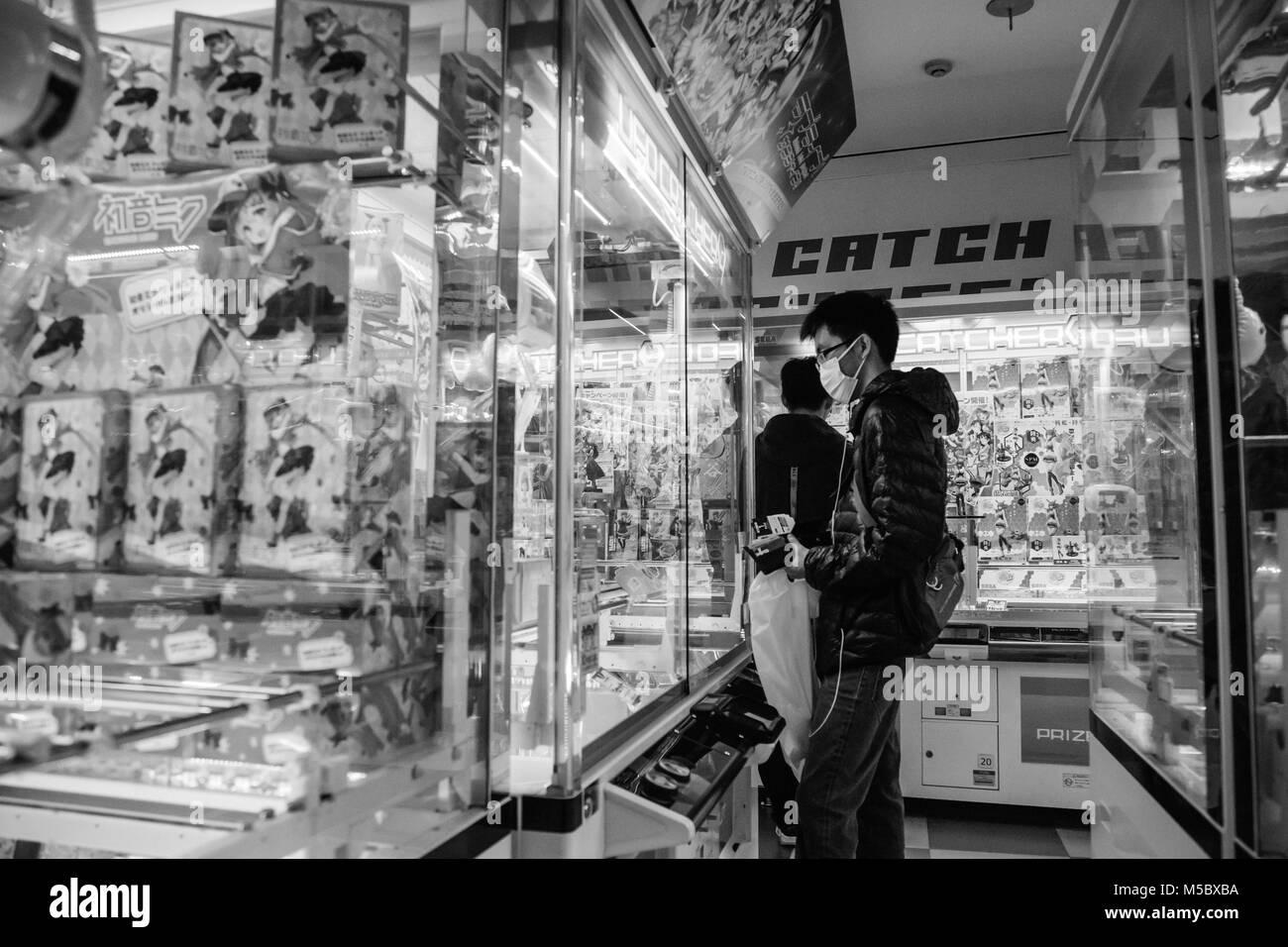 Japanese 20-somethings play arcade games for prizes in Shinjuku, Tokyo. - Stock Image