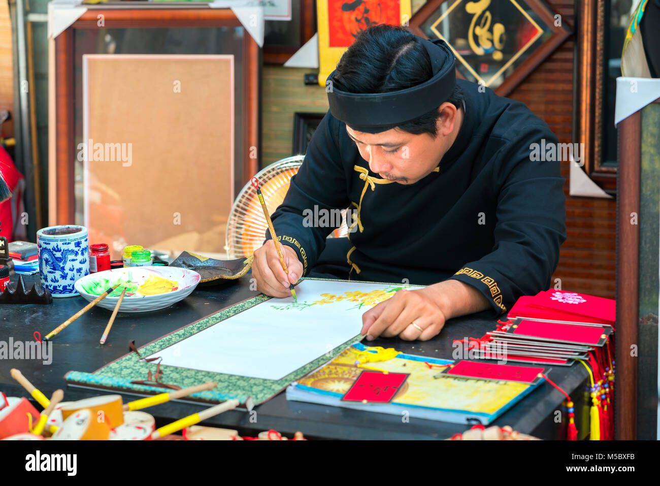 Vietnamese scholar writes calligraphy at lunar new year calligraphy festival is a popular tradition during Tet holiday - Stock Image