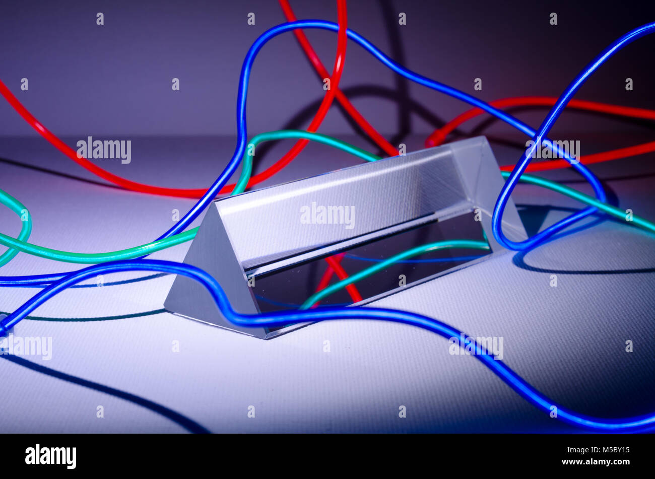 A Studio Still-life Photograph of a Triangular Glass Prism with Abstract Coloured Neon Lighting - Stock Image