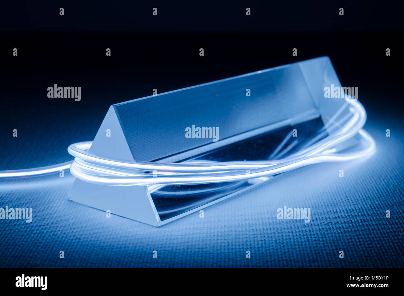 A Studio Still-life Photograph of a Triangular Glass Prism with Abstract Neon Lighting in Blue-Grey - Stock Image