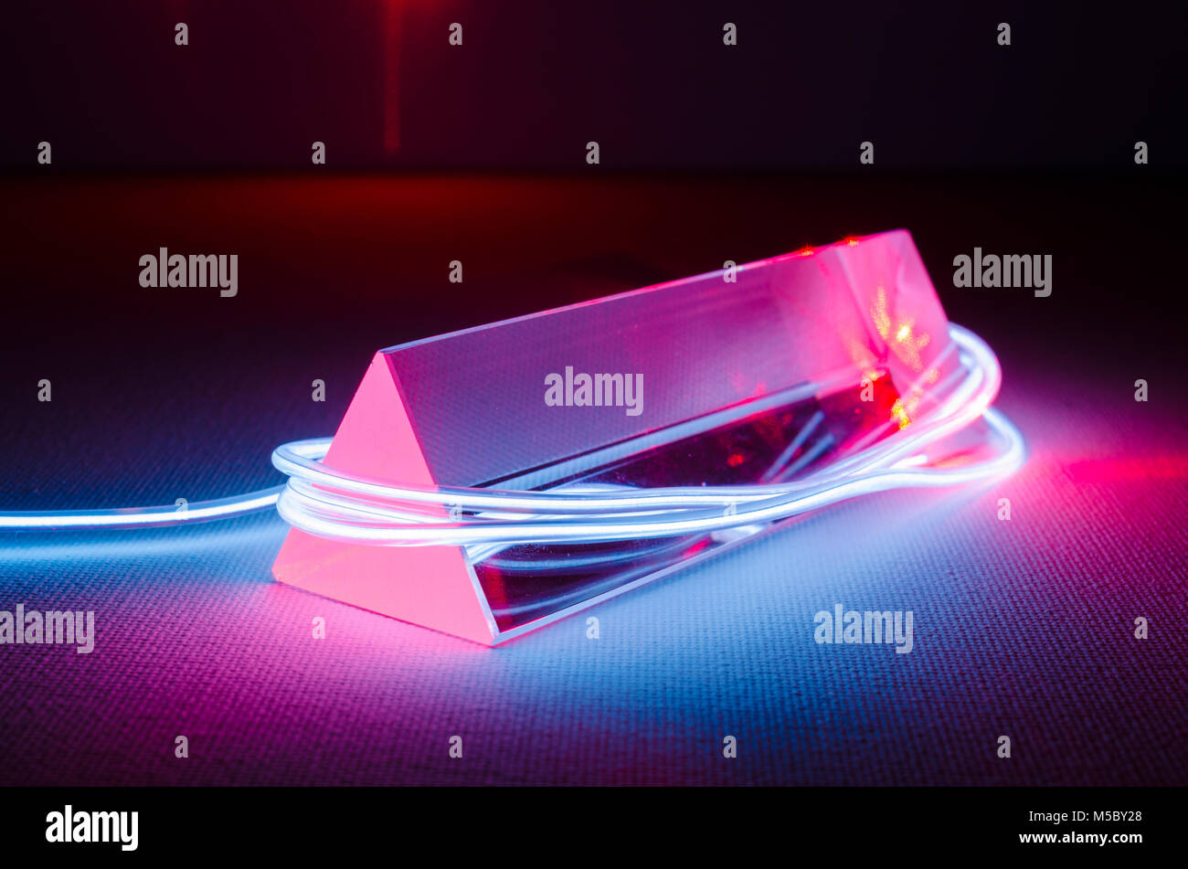 A Studio Still-life Photograph of a Triangular Glass Prism with Abstract Neon Lighting in Blue-Grey, and Red Laser - Stock Image