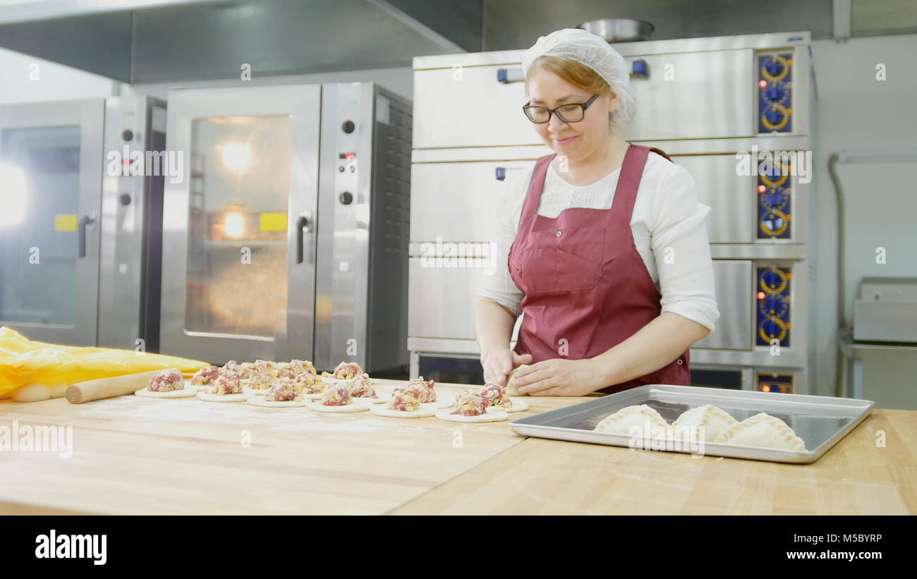 Adult woman in glasses bakes cakes in the bakery - Stock Image