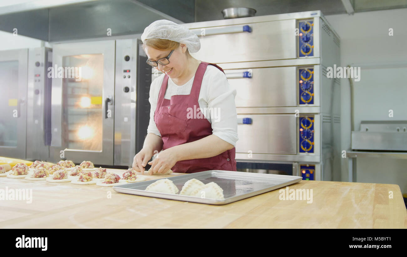 Adult woman in glasses and apron bakes cakes in the bakery - Stock Image
