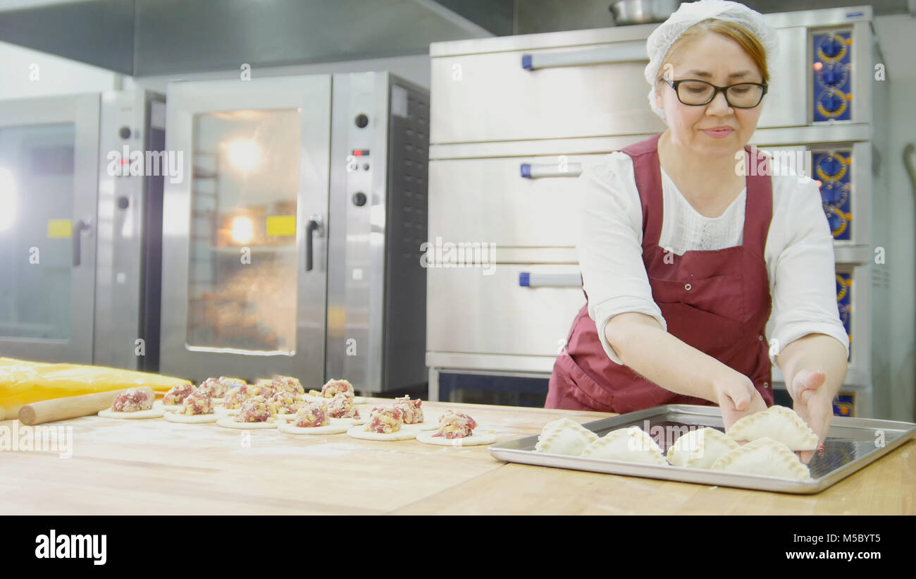 Adult woman in glasses and apron bakes cakes in the bakery face - Stock Image