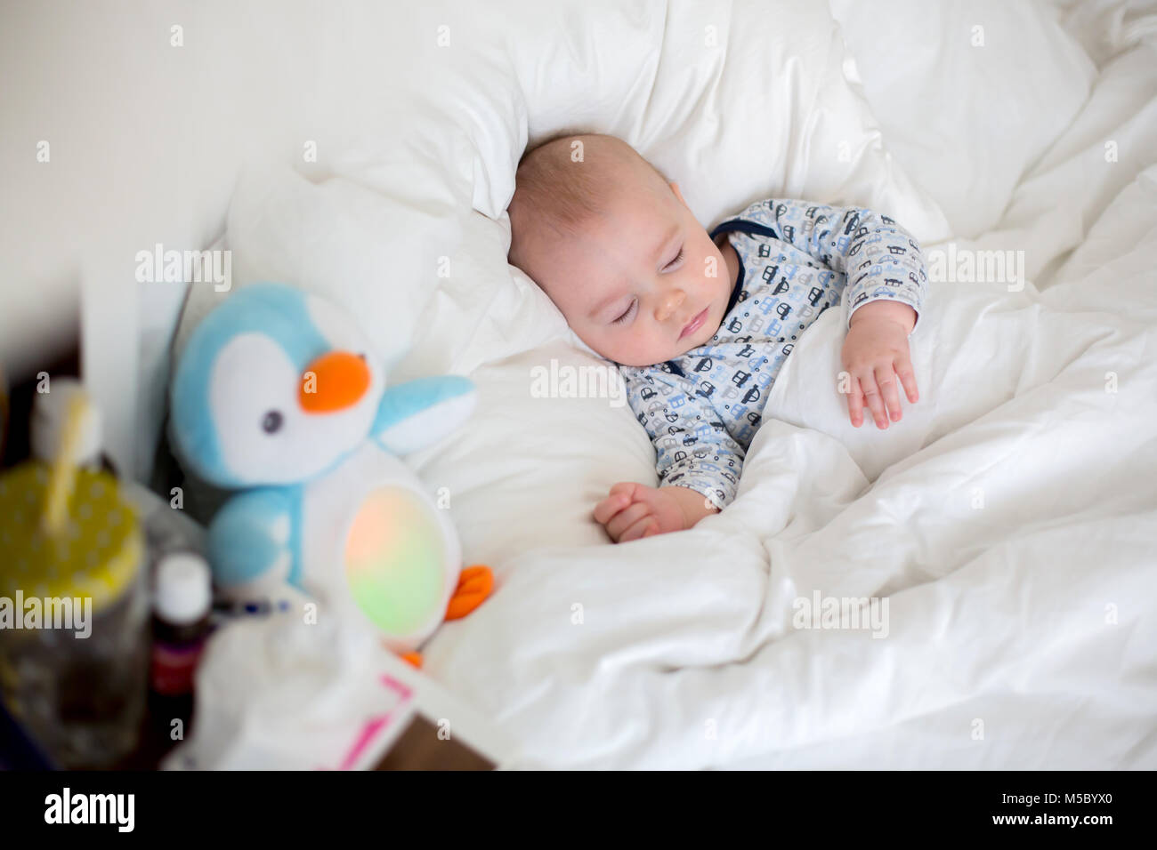 Sick chidl, bab boy lying in bed with a fever, resting at home - Stock Image