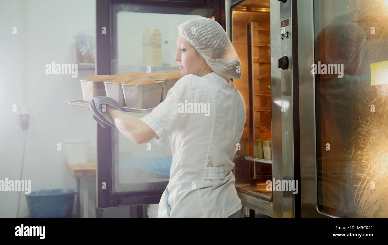 Female bakes on commercial kitchen - pulls the bread from the oven - Stock Image