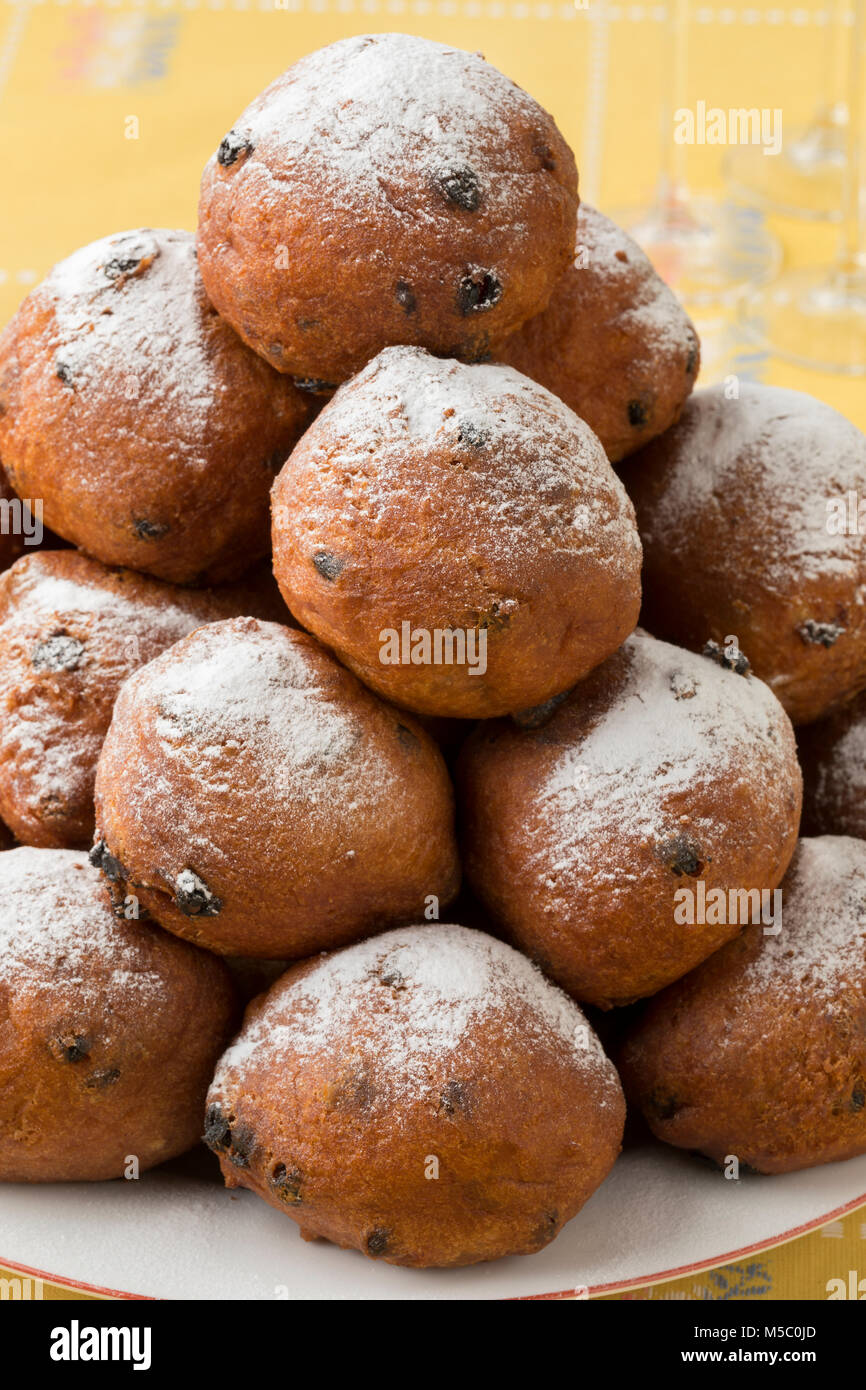 Heap of oliebollen on a dish, close up, traditional Dutch pastry for New Year's Eve - Stock Image