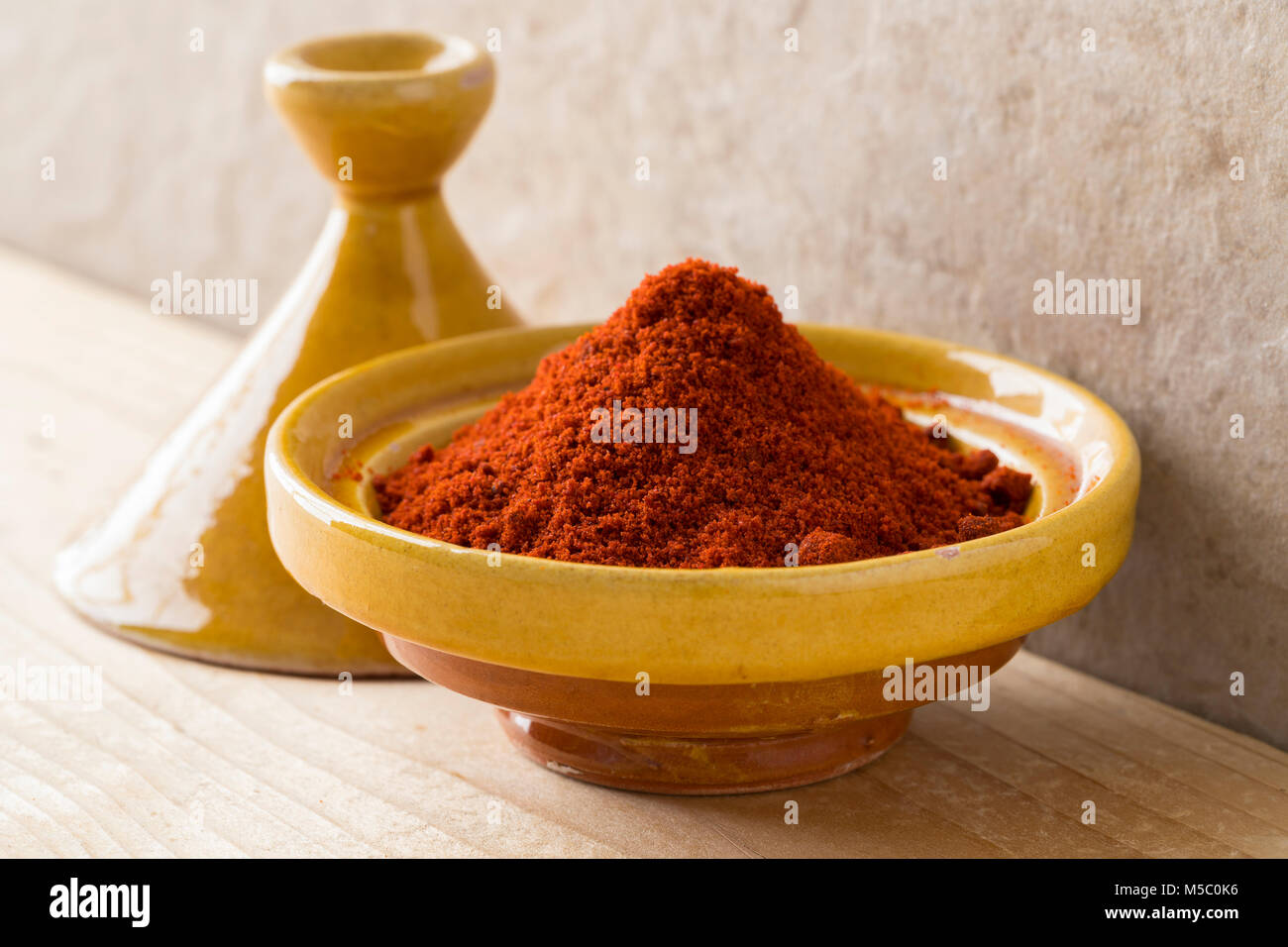 Traditional yellow bowl with Moroccan dried ground paprika - Stock Image