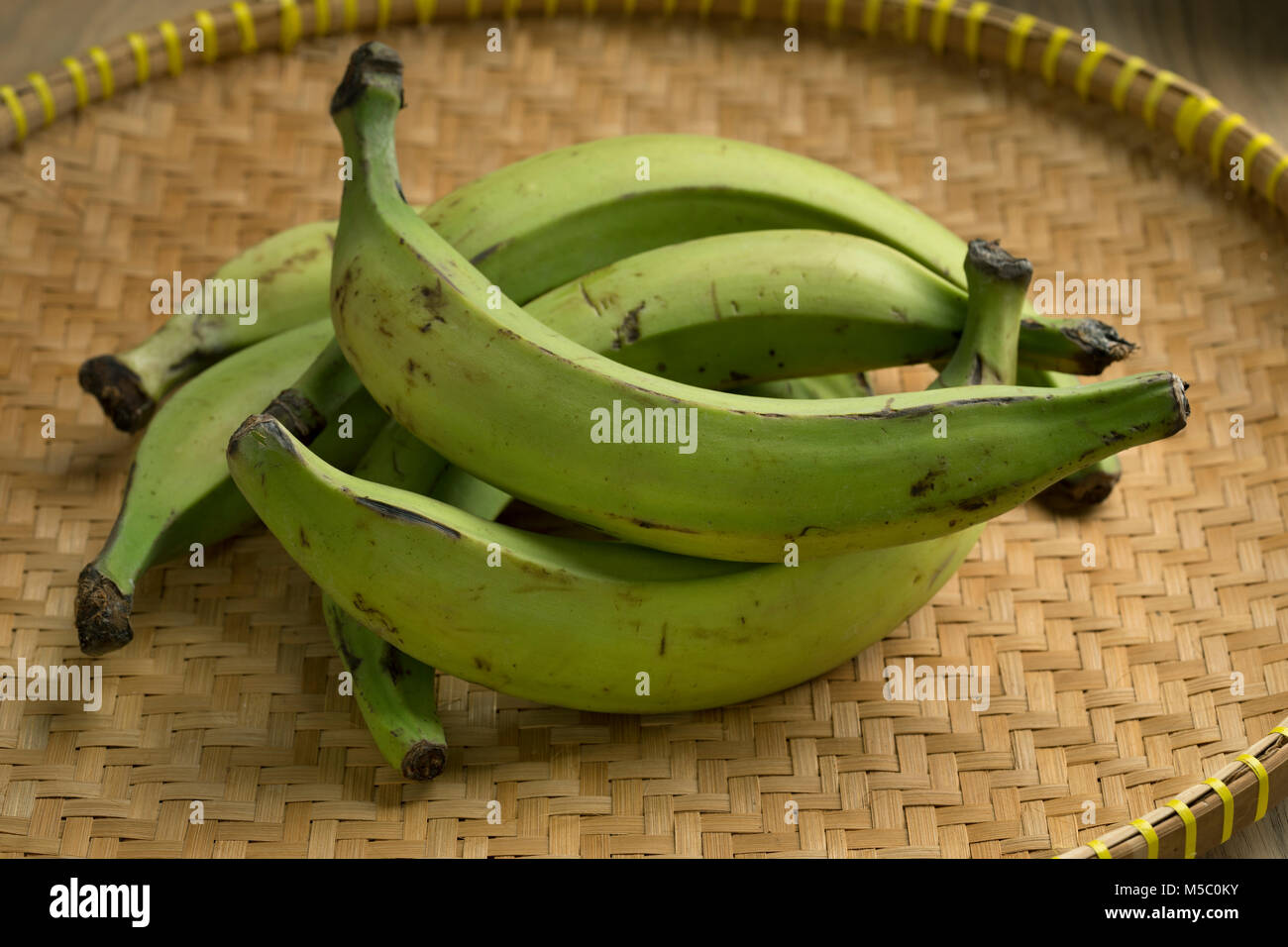 Basket with fresh green unripe bananas - Stock Image