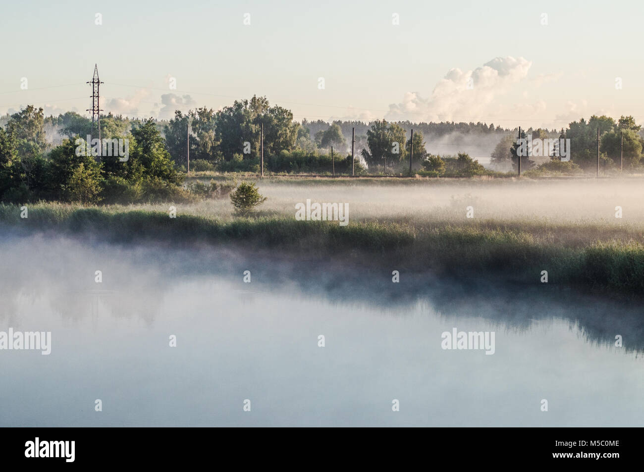 White morning fog over a green grass field near the lake. - Stock Image