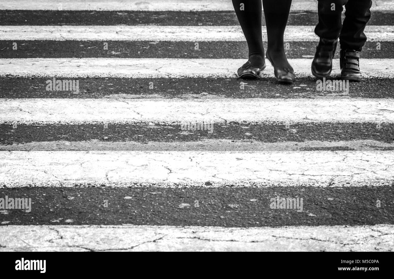 People walking on a zebra crossing. Black and white shot. Urban and cityscape concept - Stock Image