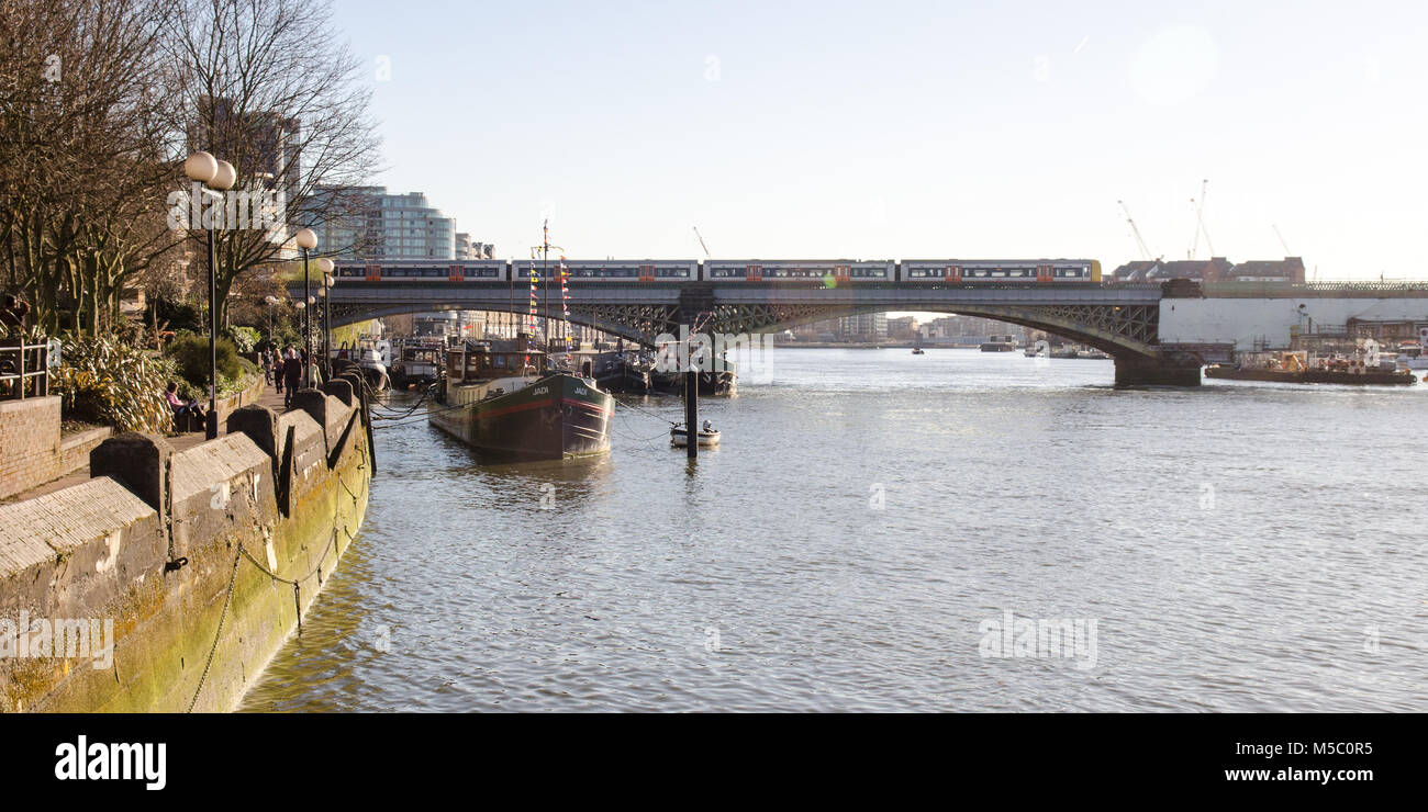 London, England, UK - March 16, 2014: A Class 378 London Overground passenger train crosses the River Thames between - Stock Image