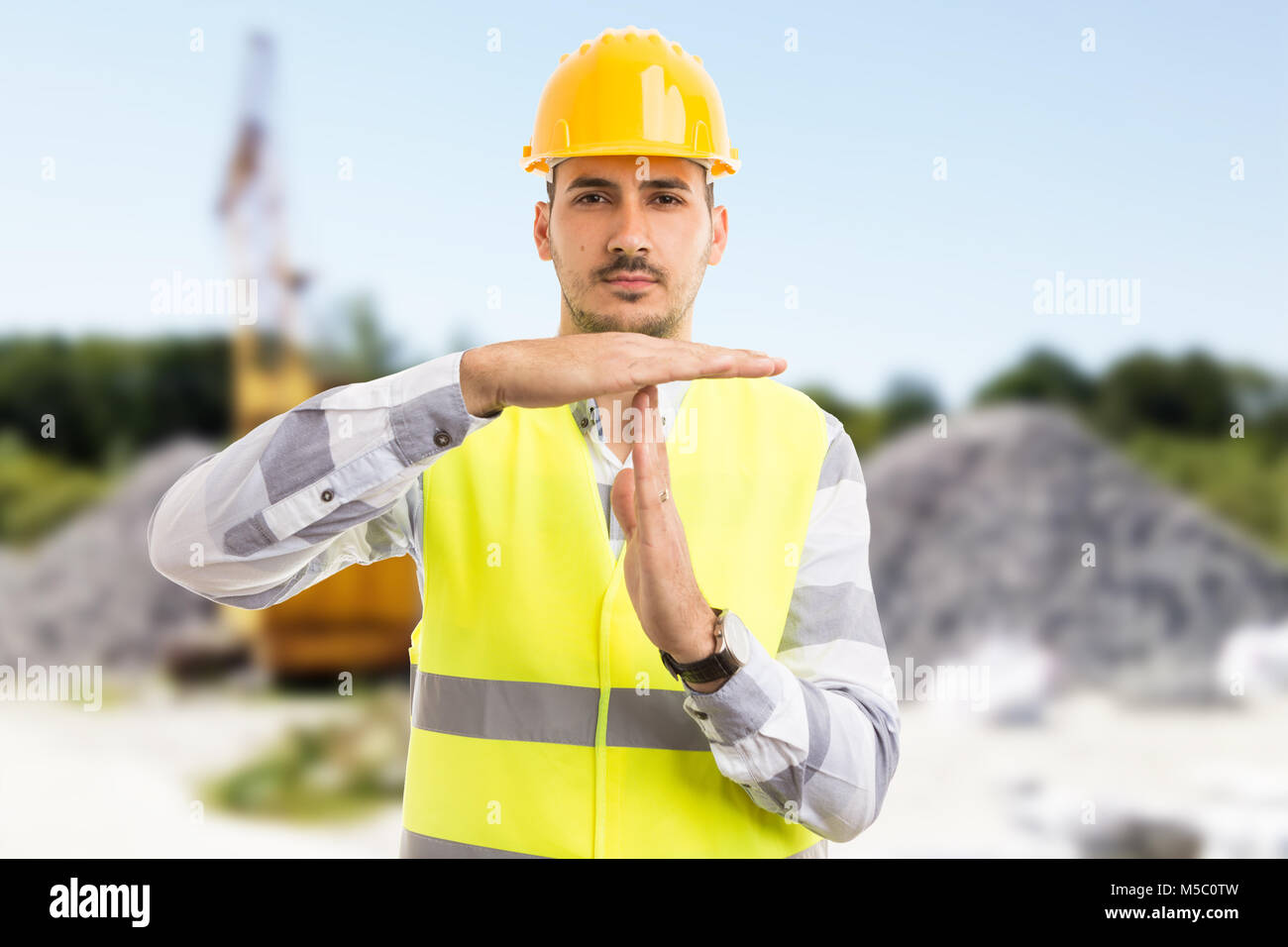 Architect or engineer making time out pause break gesture on construction site or pit outdoors - Stock Image