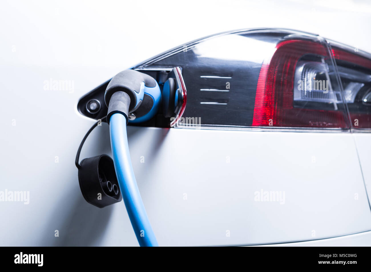 Full electric Tesla car charging picture with plug-in connector as renewable energy green fuel stations concept Stock Photo