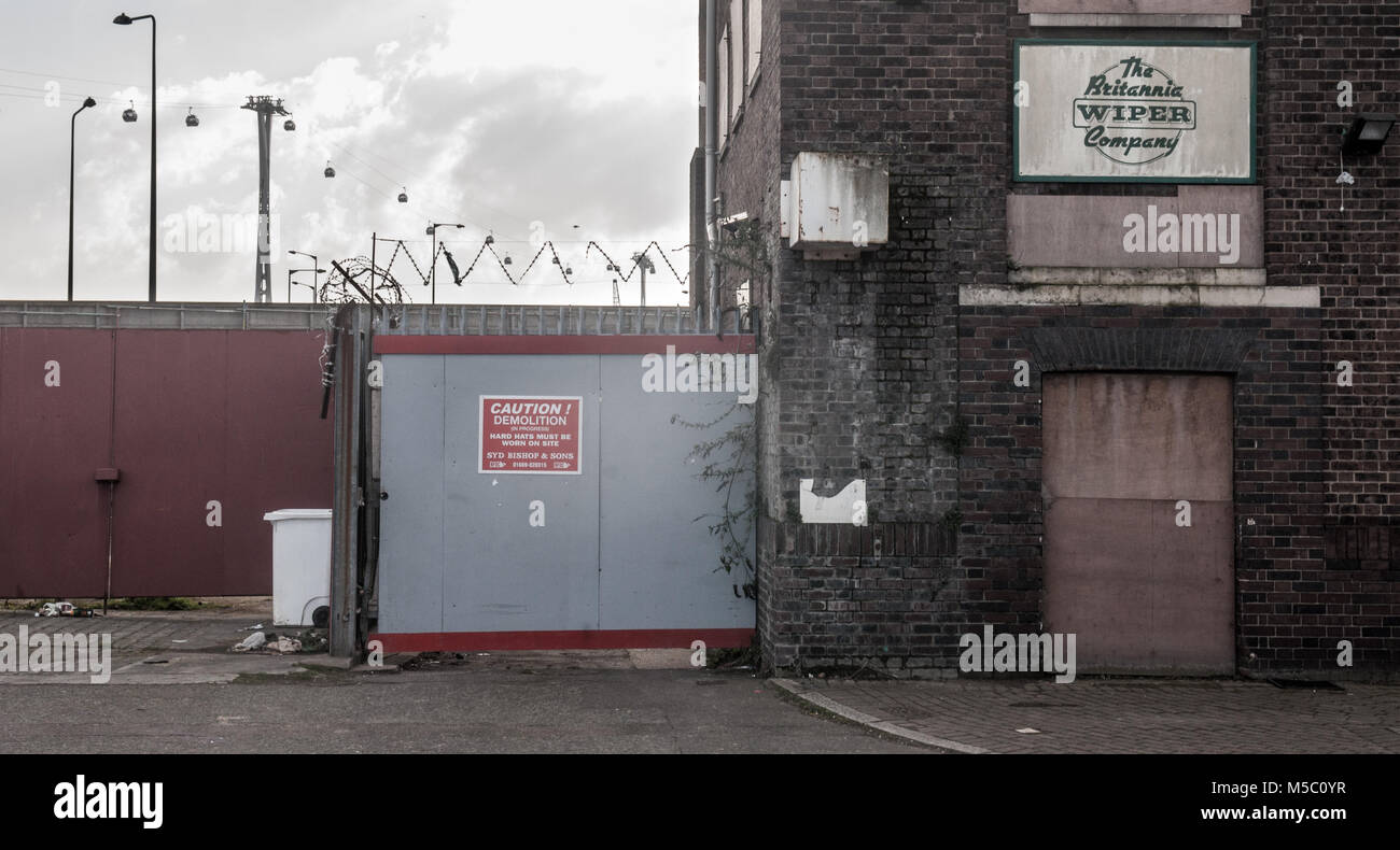 London, England, UK - February 17, 2013: The modern Thames Cable Car rises behind boarded up industrial warehouses - Stock Image