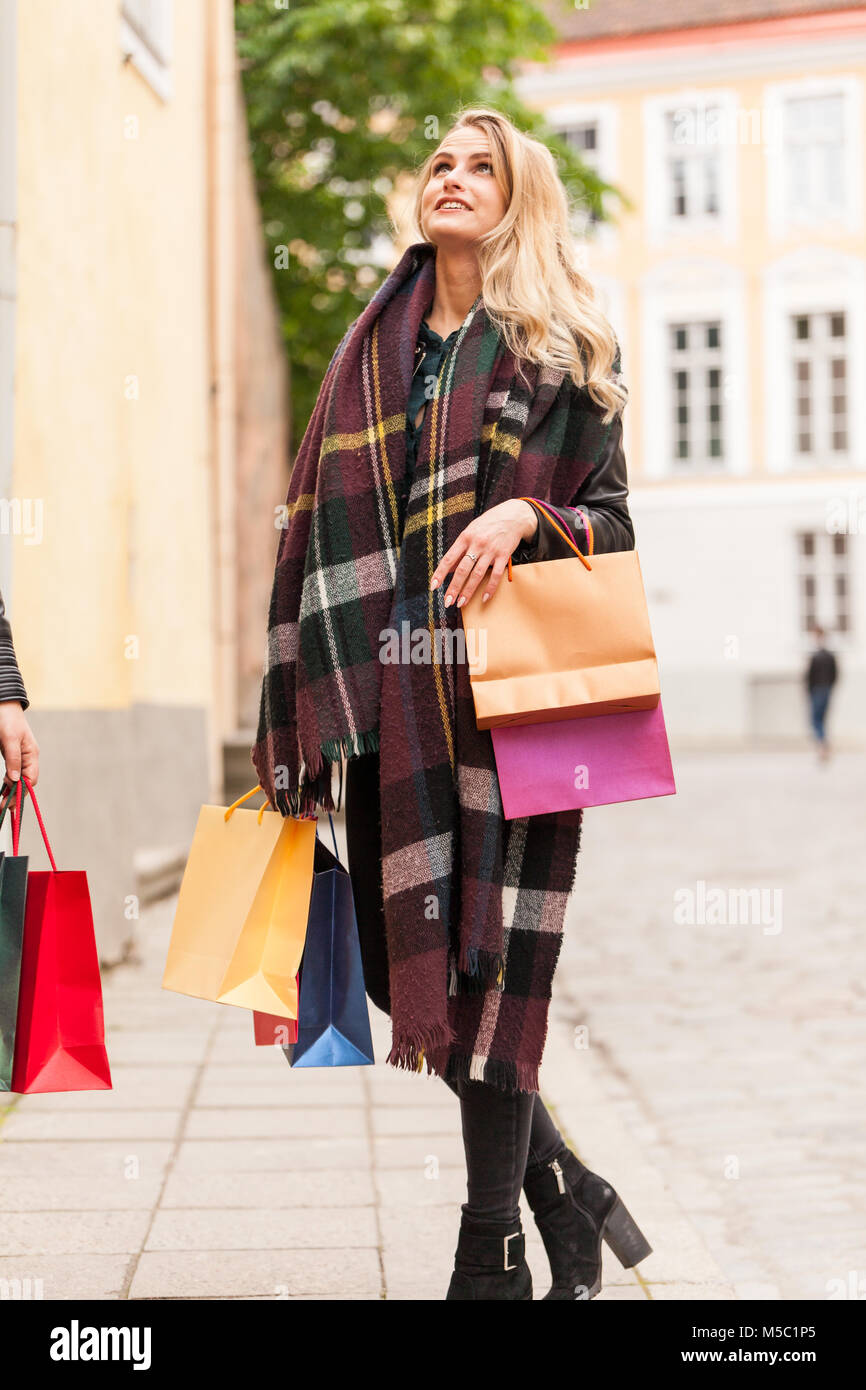 Beautiful shining girl outdoor in cold weather with bags full of products - Stock Image
