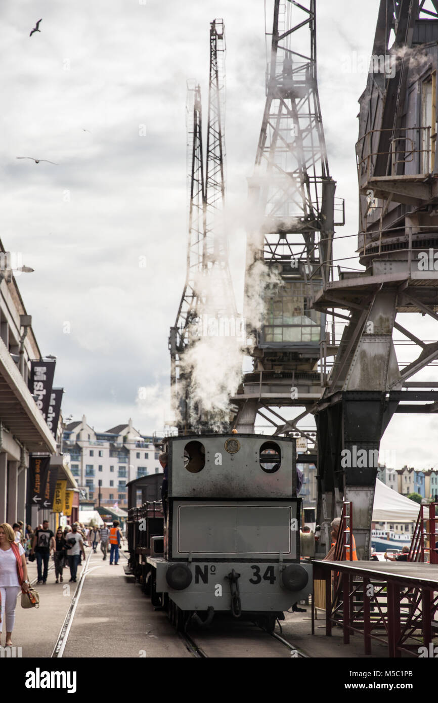 Bristol, England - July 17, 2016: A preserved steam shunting engine passes old dockside cranes and warehouses at - Stock Image