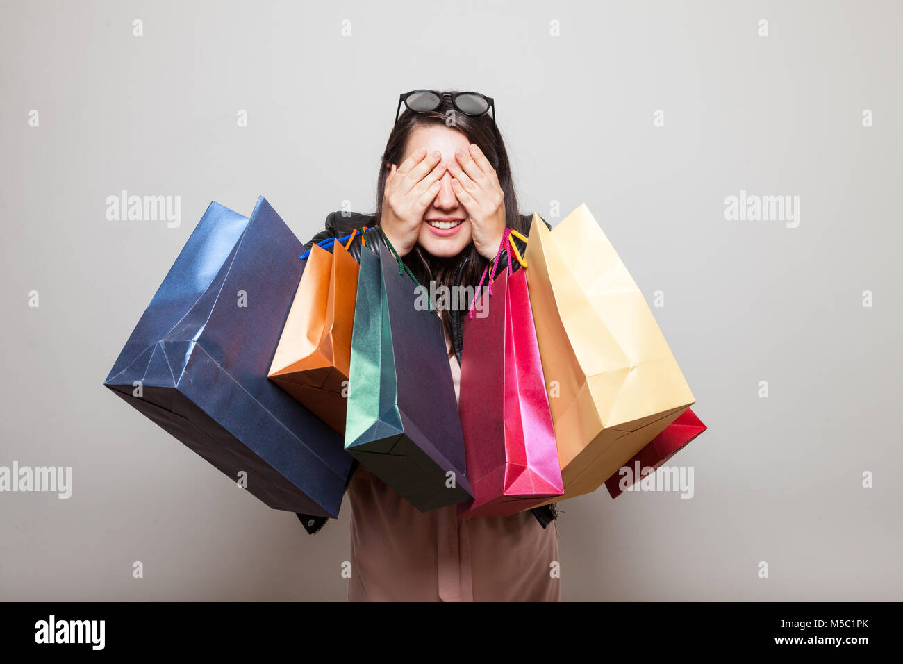 Beautiful smiling caucasian girl closes eyes and guessing what is in the gift bags she holds - Stock Image