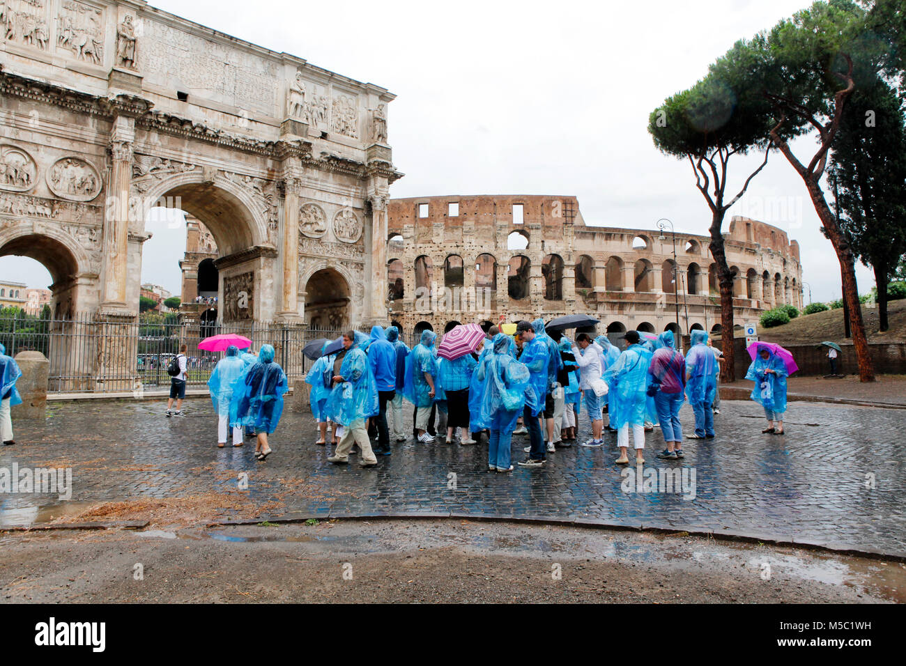 Tourists wearing ponchos in the rain at the Colosseum in Rome - Stock Image