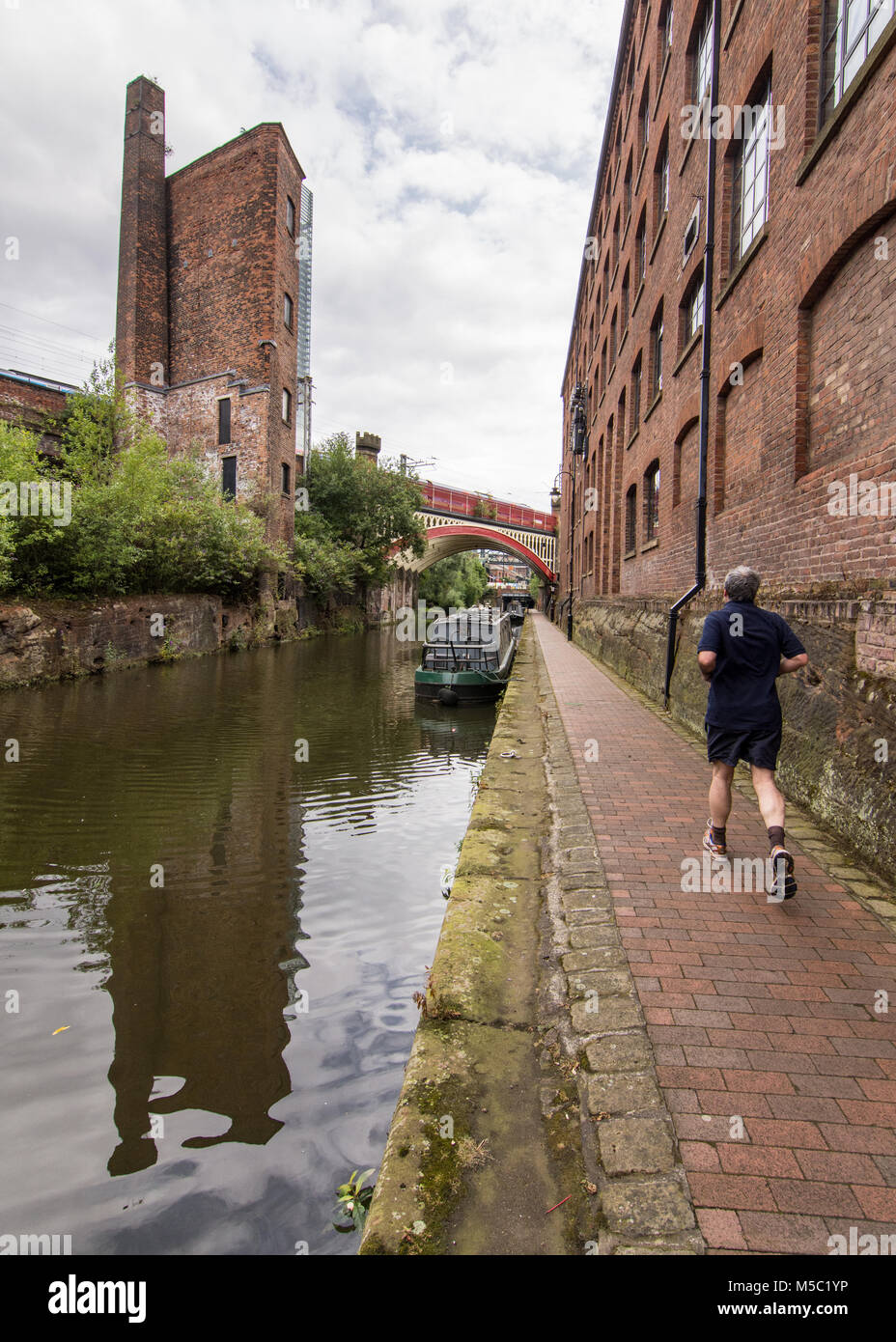 Manchester, England, UK - August 2, 2015: A jogger runs on the towpath of the Bridgewater Canal beside industrial - Stock Image