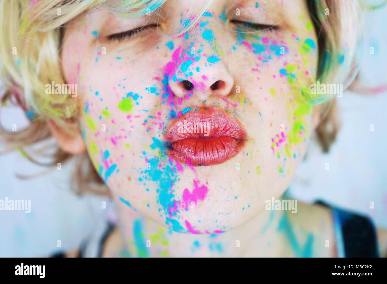 Young beautiful woman with paint in her face - Stock Image