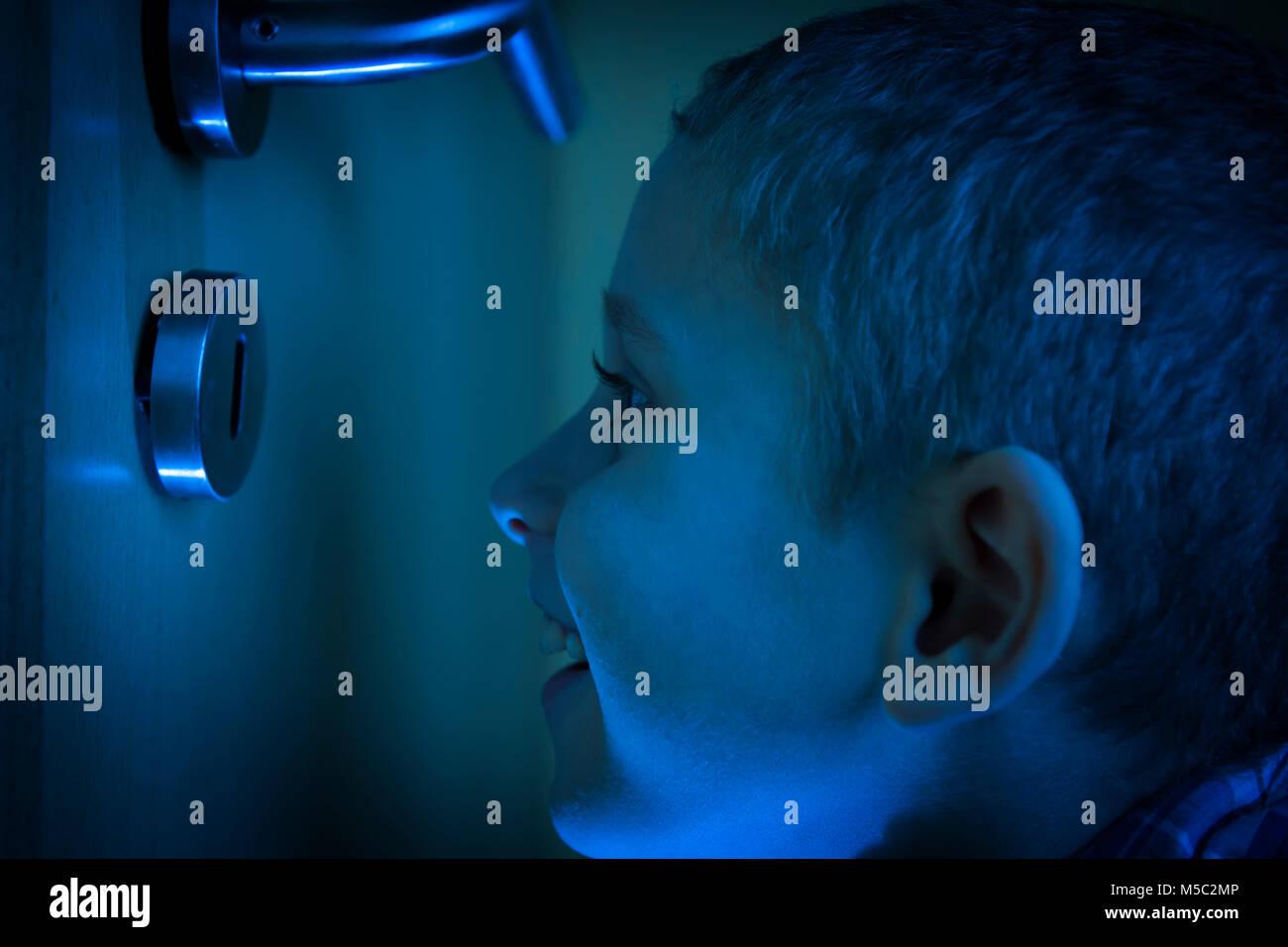 Junge im dunklen Zimmer blickt im Schein der Taschenlampe durch ein Schlüsselloch. Stock Photo
