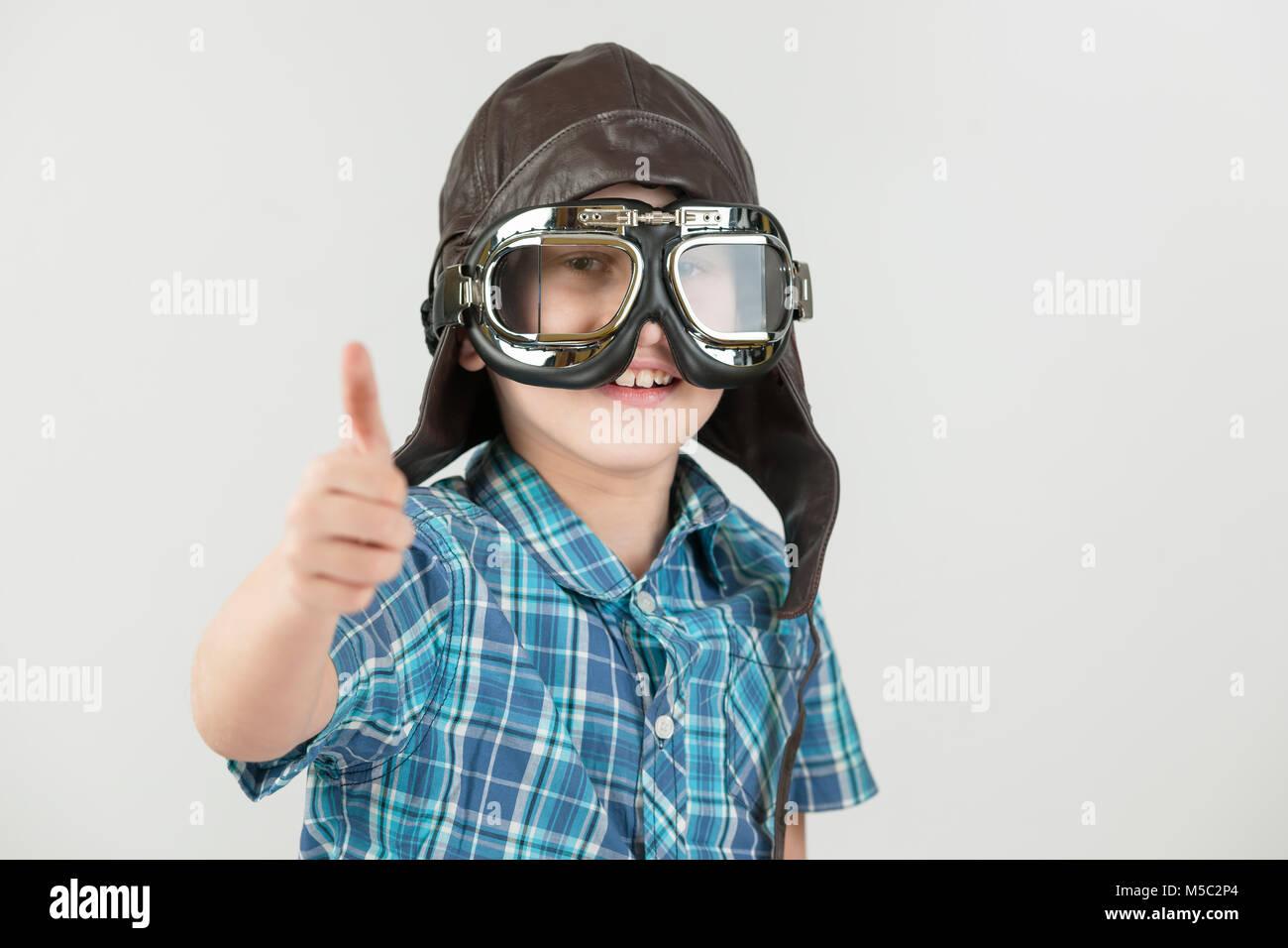 Vor grauem Hintergrund freigestellte Oberkörper-Ansicht eines zehnjährigen Jungen im blau-karierten kurzärmligen - Stock Image
